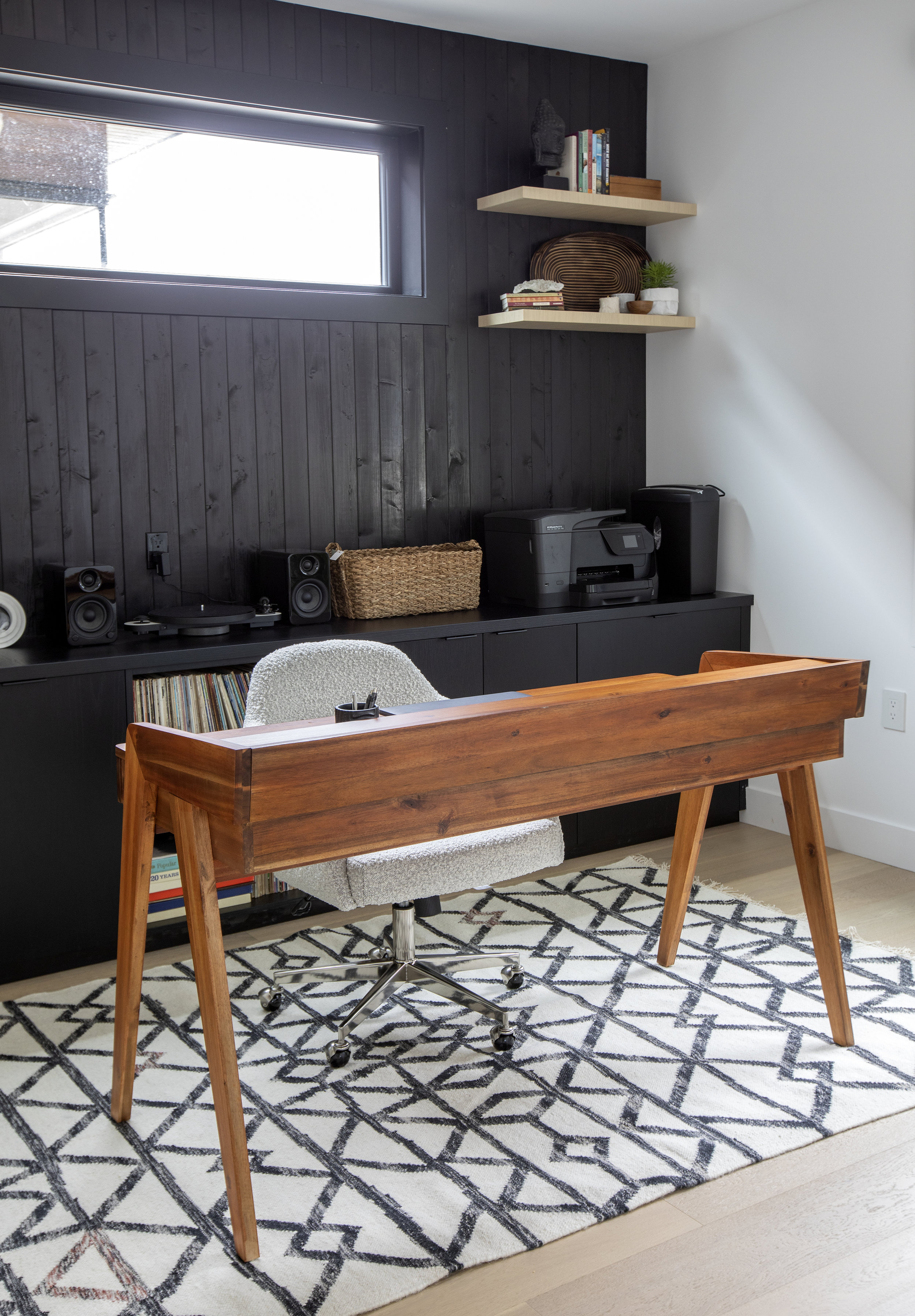 The wooden writing desk in East 13th Street sits on top of a black and white geometric rug.