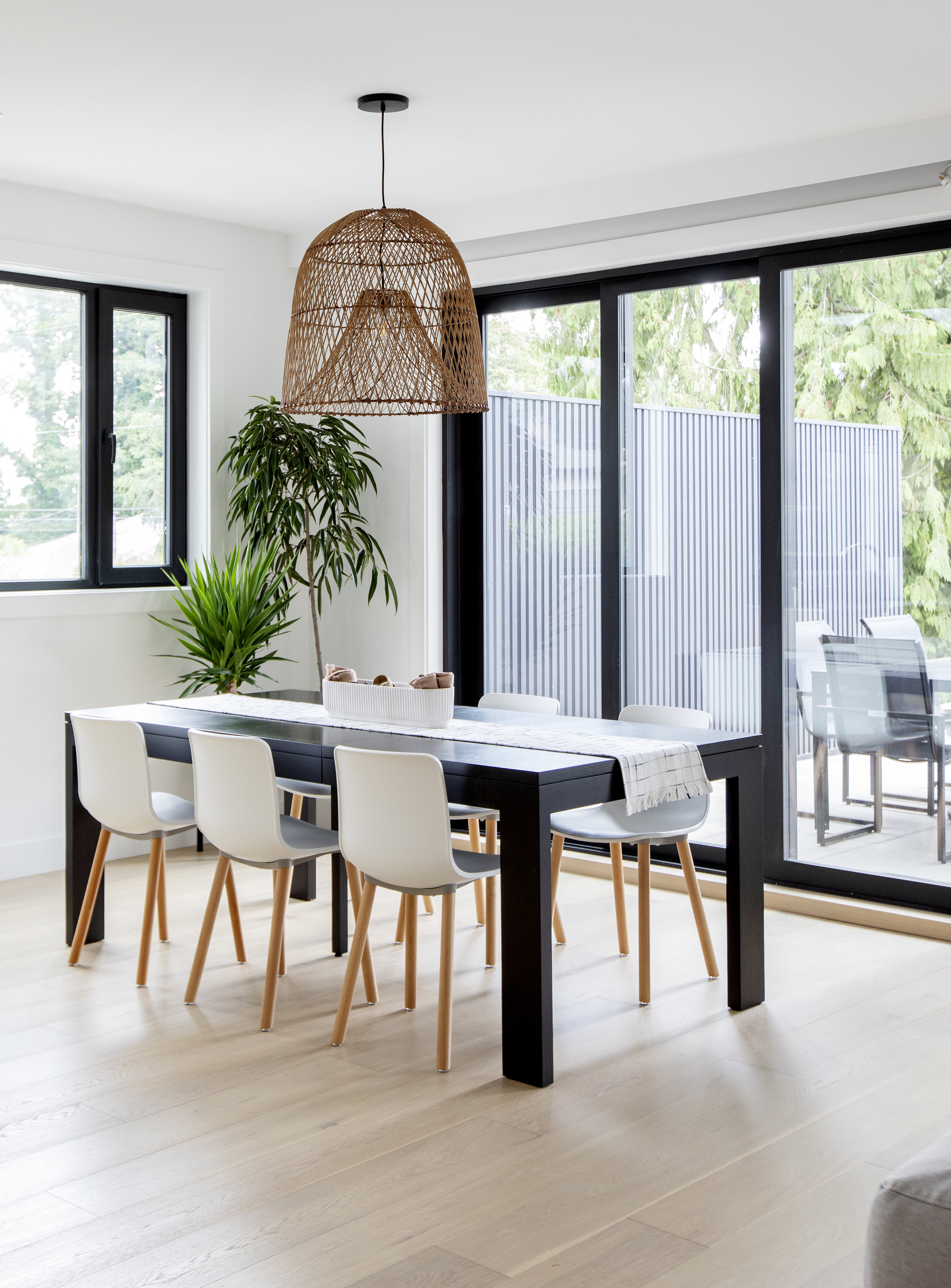 The family dining room has a large black dining table surrounded by white chairs, with a wicker light fixture positioned above.