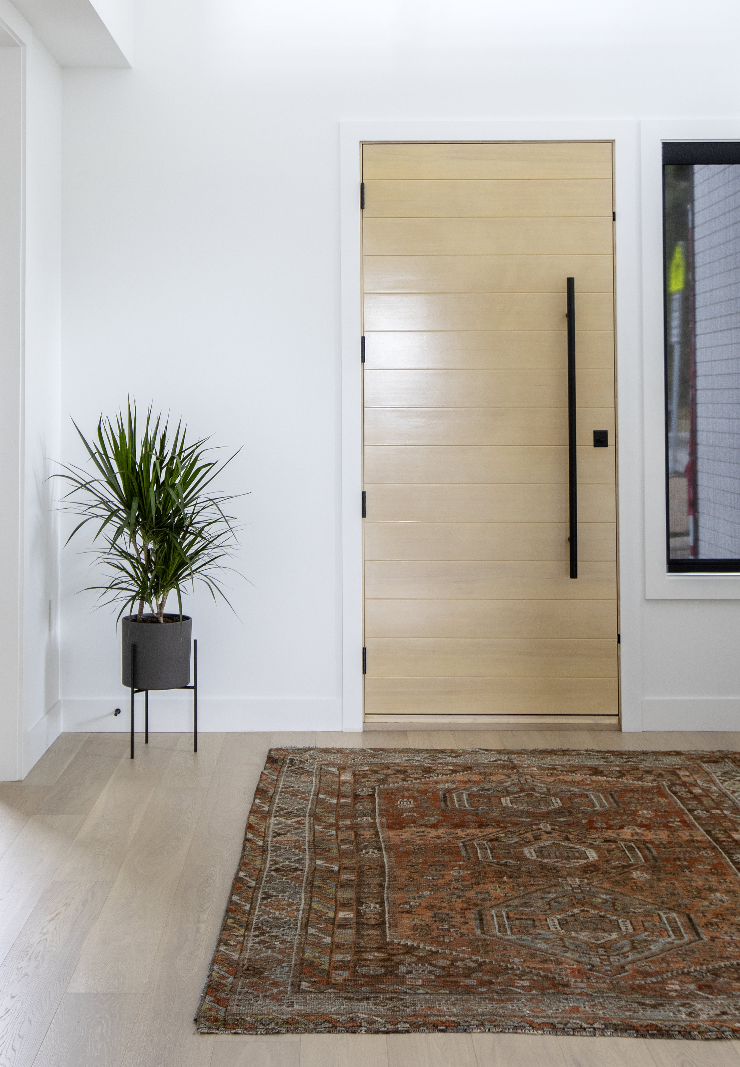 The custom front door of East 13th street is comprised of wooden slats and a large vertical bar, flanked by a beautiful maroon oriental rug.
