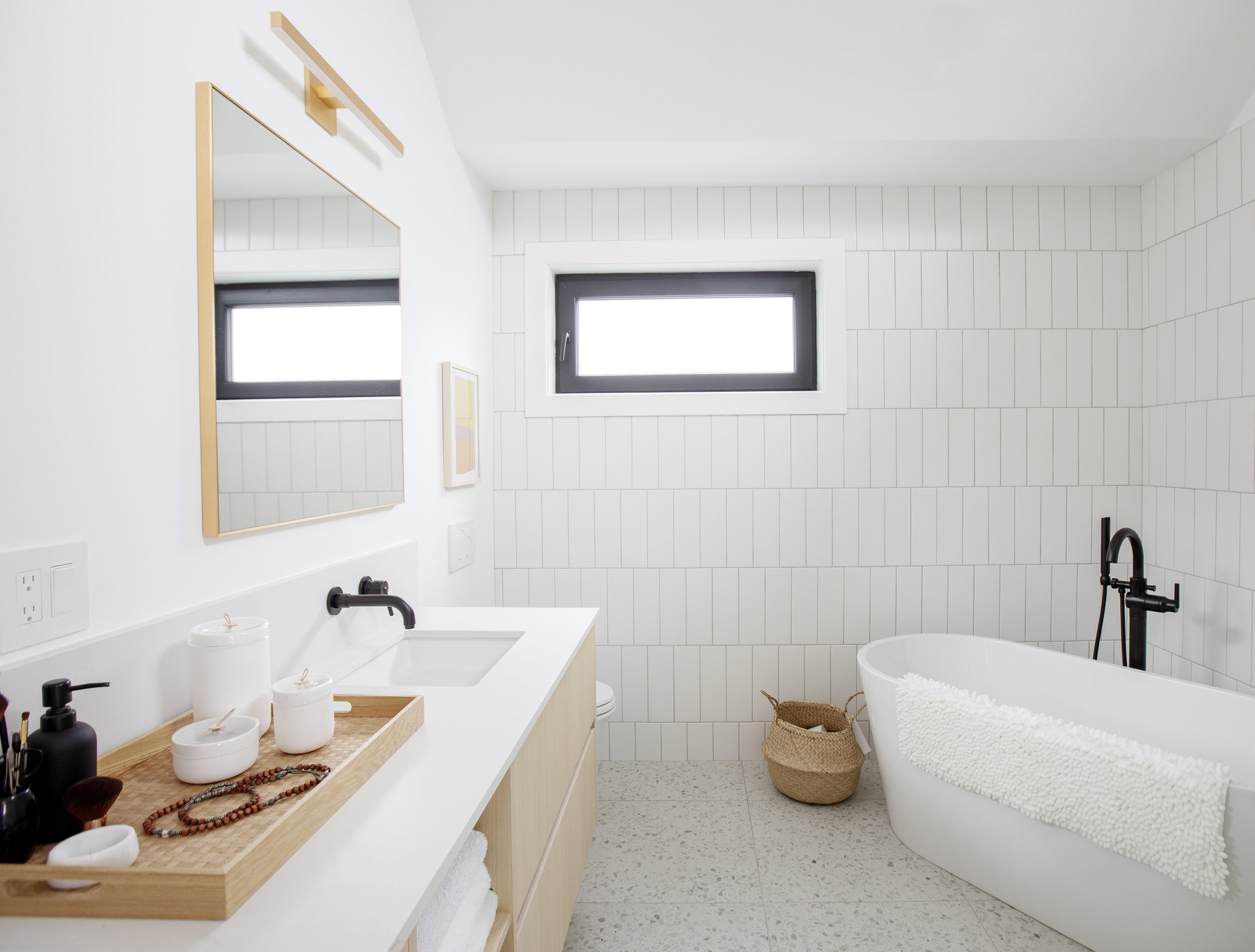 The master bathroom of East 13th Street is modern and crisp, with white countertops, chrome fixtures and a large freestanding soaker tub.