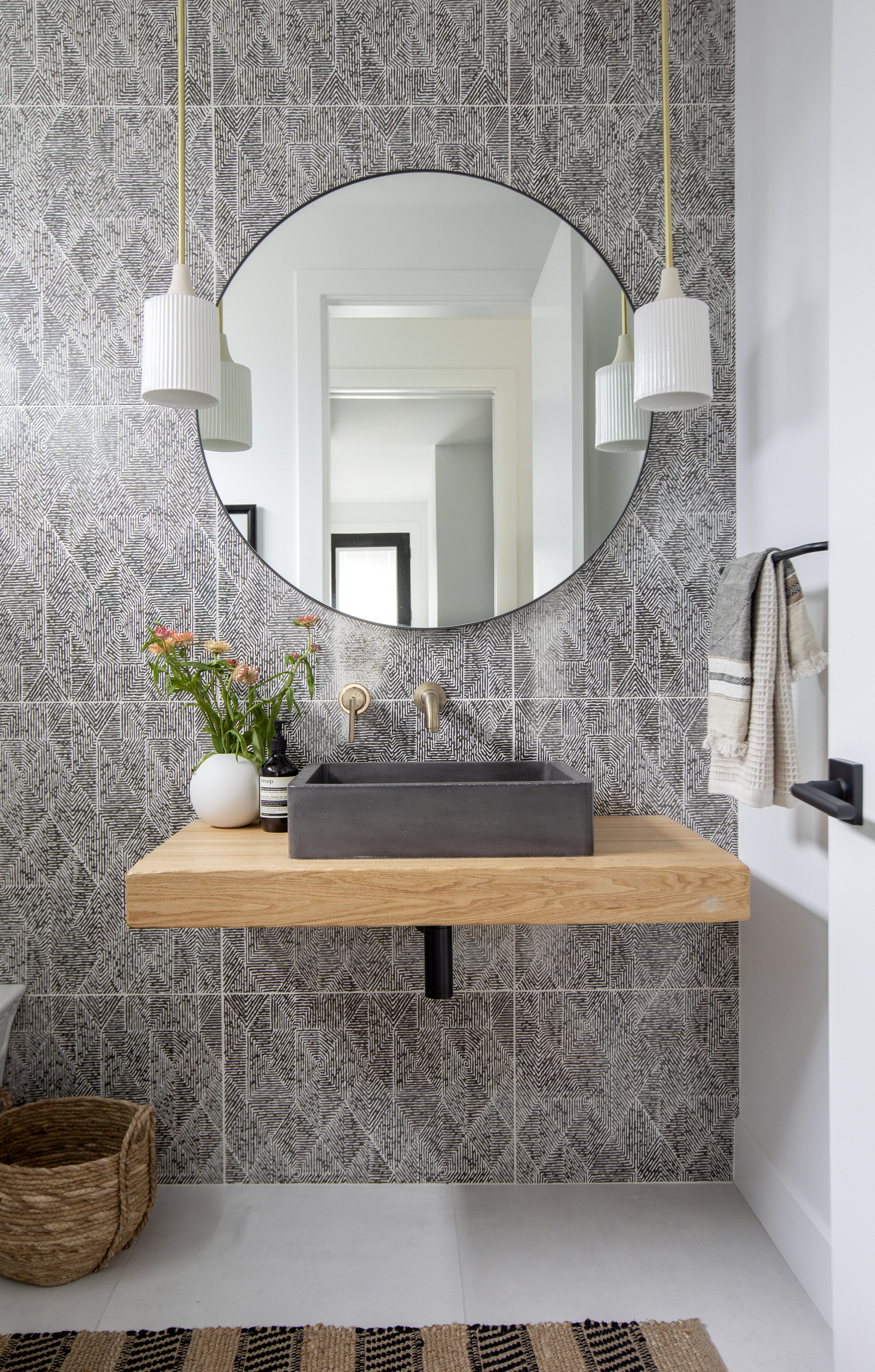 The modern bathroom in East 13th Street has a patterned black and white wallpaper and a square concrete sink, complete with gold faucet details.