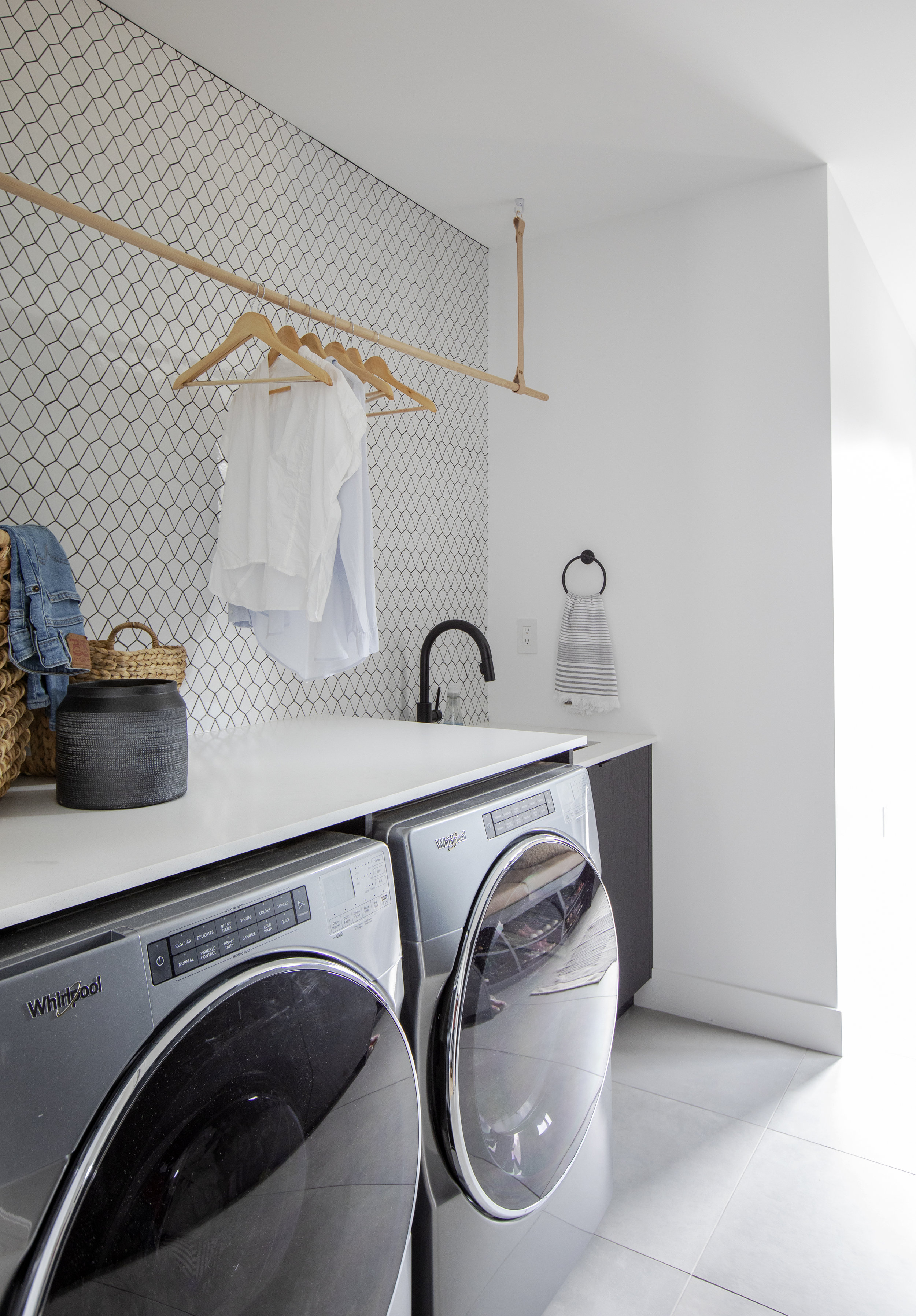 The laundry room of East 13th Street has a black and white geometric patterned wall, complete with an overhanging bar to hang shirts to dry.