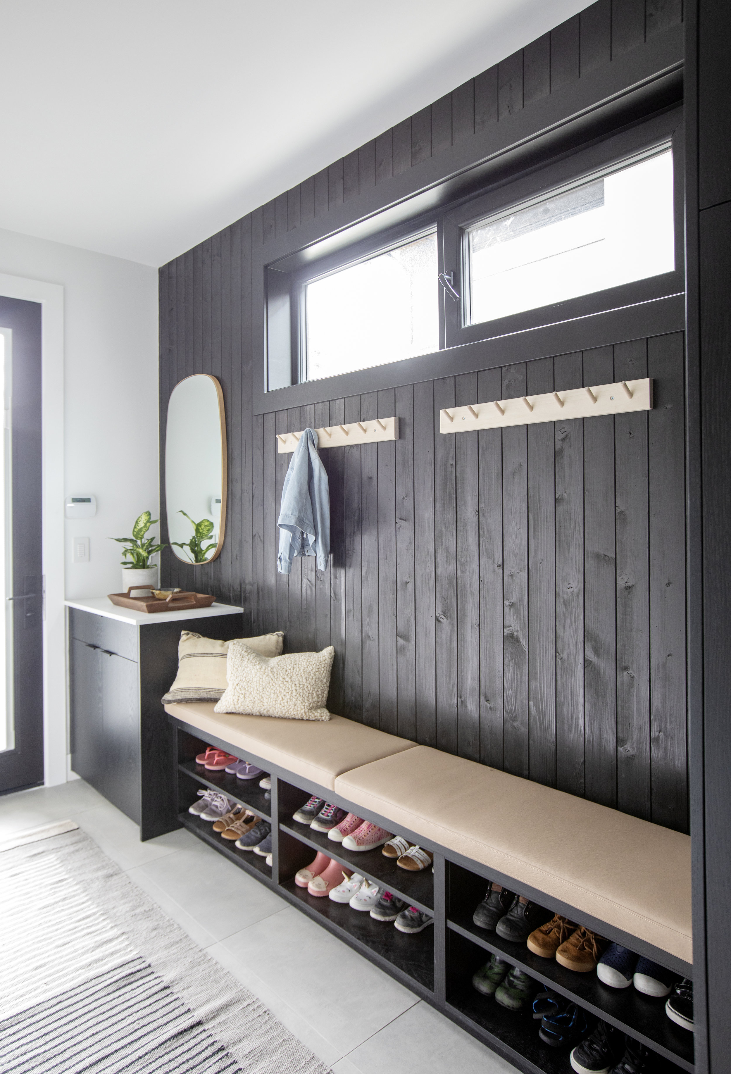 The mudroom of East 13th Street has a dark wooden panelled accent wall with a long bench in front of it with built in shoe rack for the whole family.