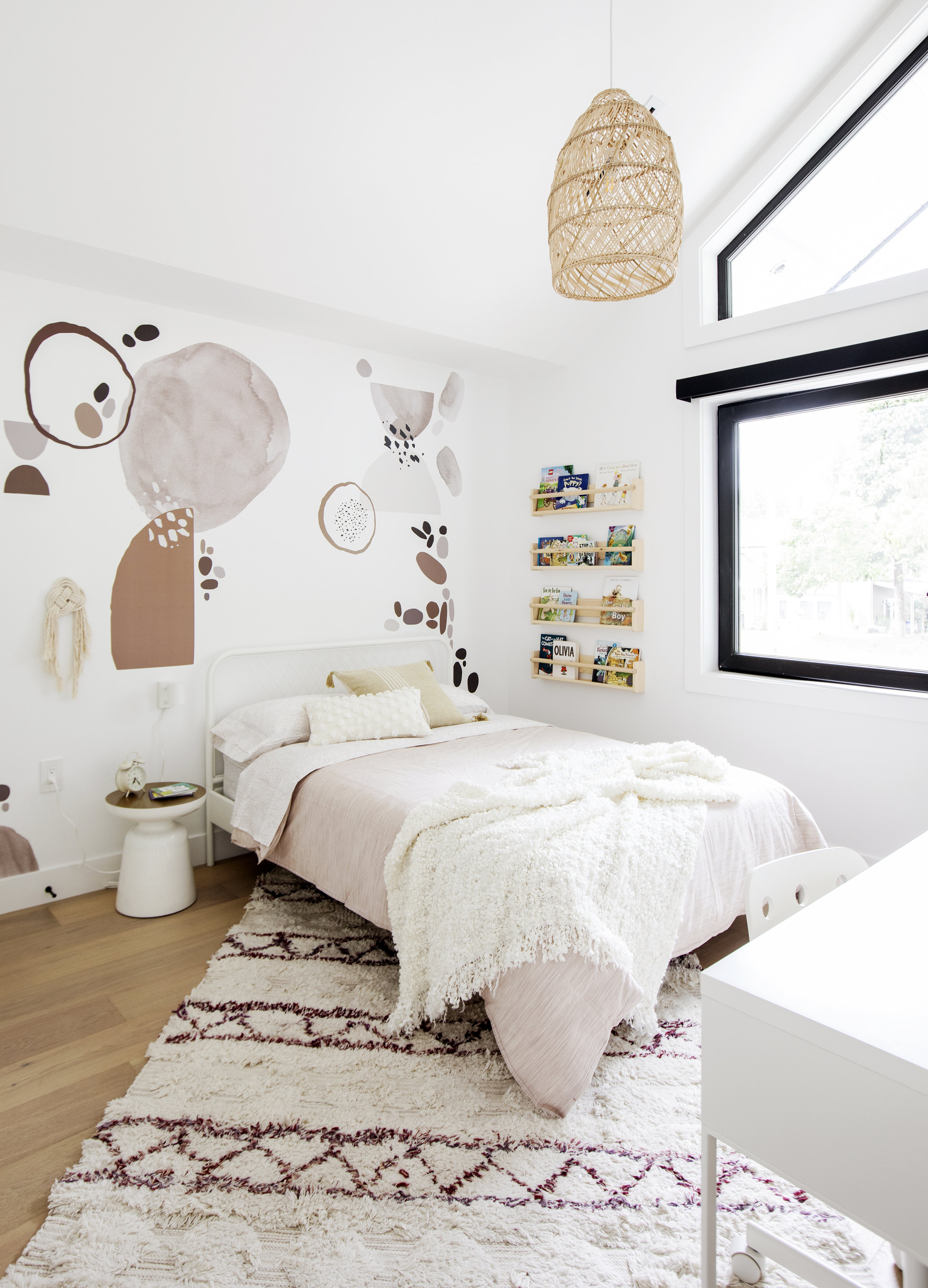 A child's bedroom in East 13th Street, complete with a comfortable pink twin bed and custom book rack built into the wall next to it.