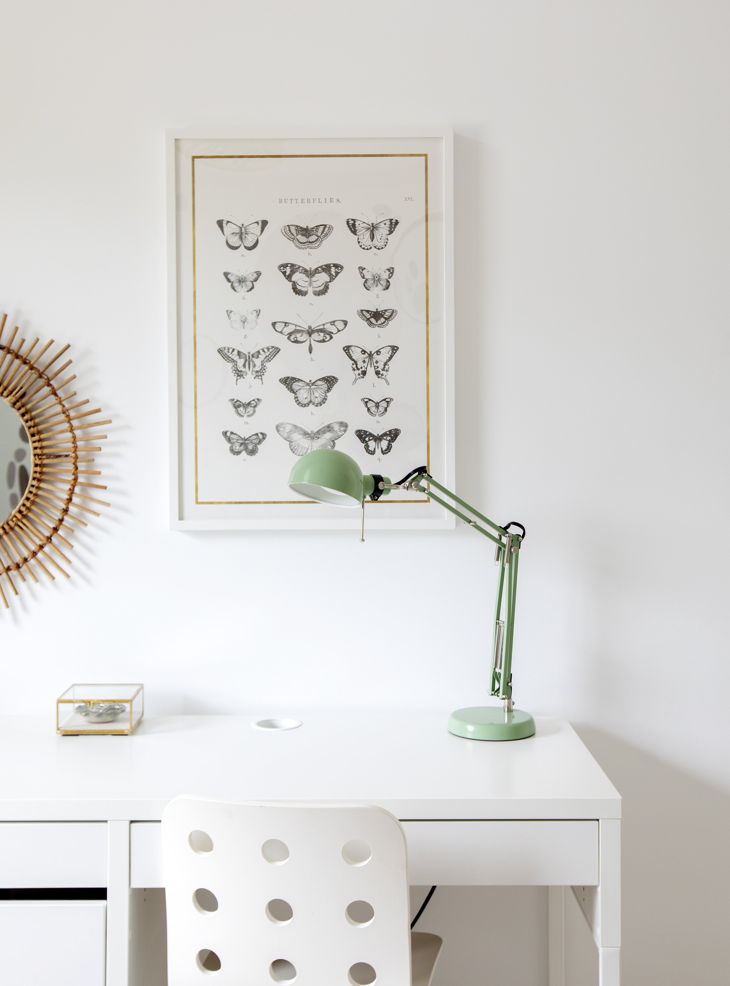 A homework desk contains a mint green lamp and faces a framed poster of butterflies.