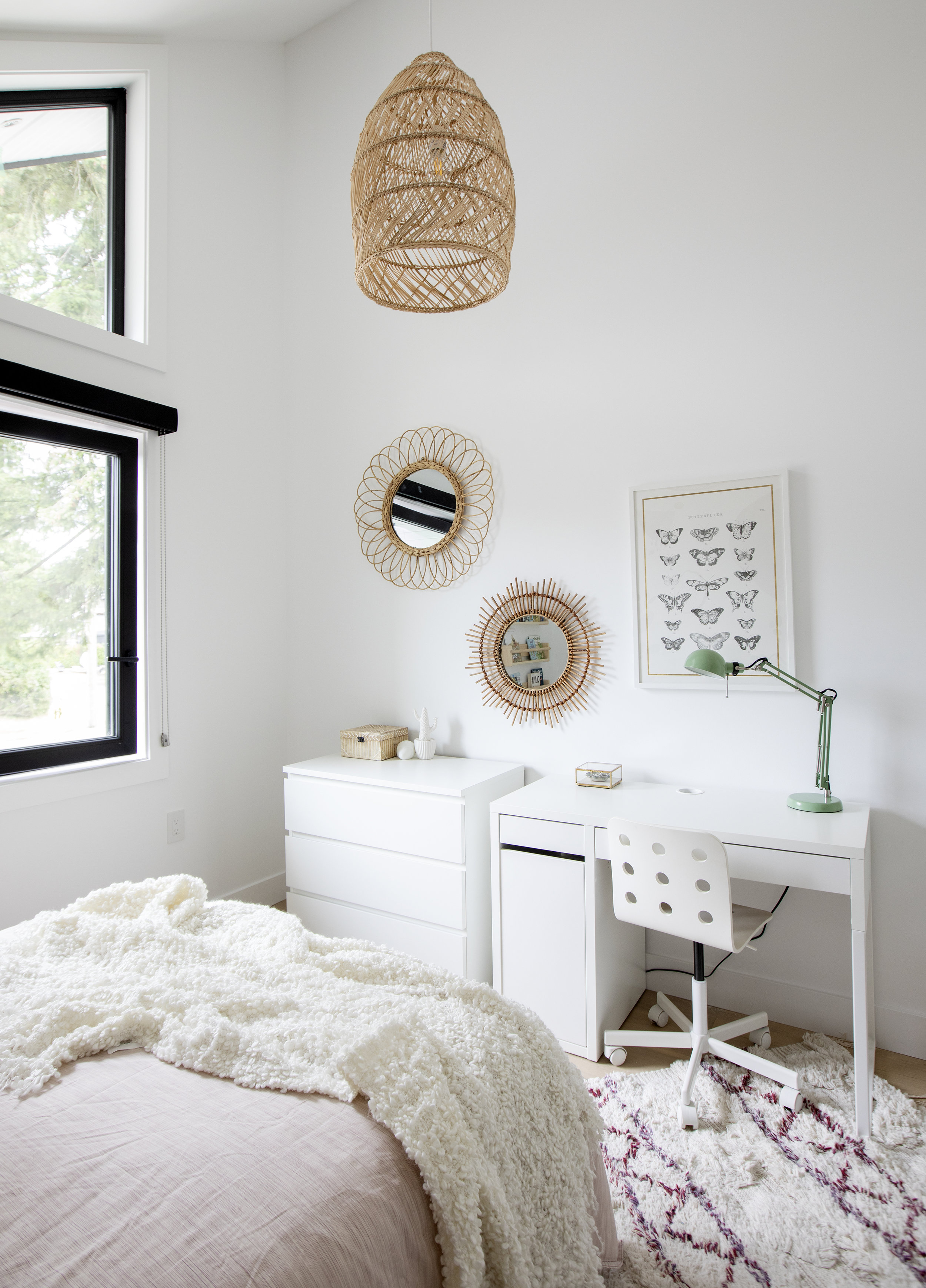 A large shot of the wall opposite the bed in a child's bedroom in East 13th Street contains two mirrors, a framed poster, a white dresser drawer and desk.