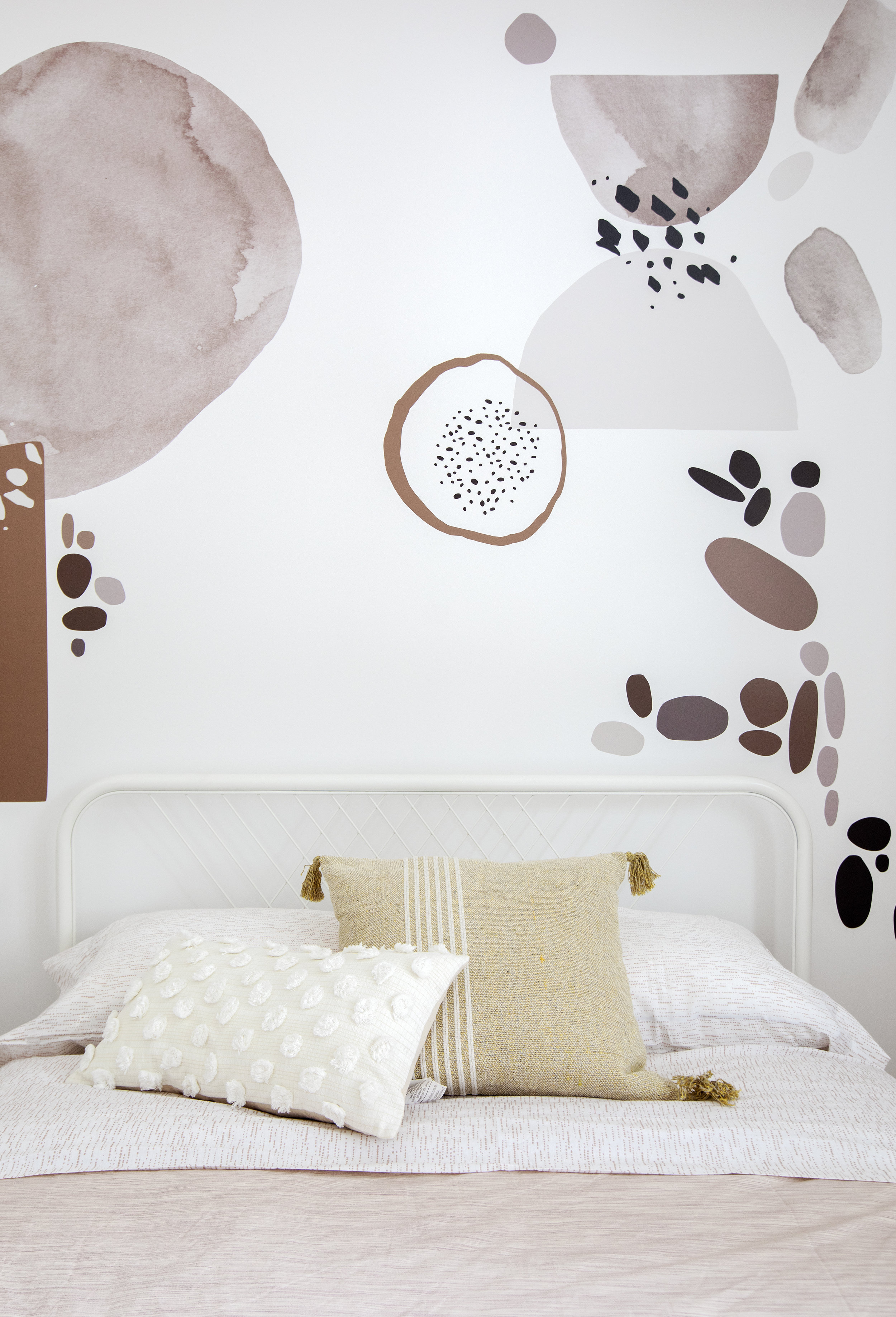 An accent wall of pink organic shapes sits directly behind a child's bed in East 13th Street