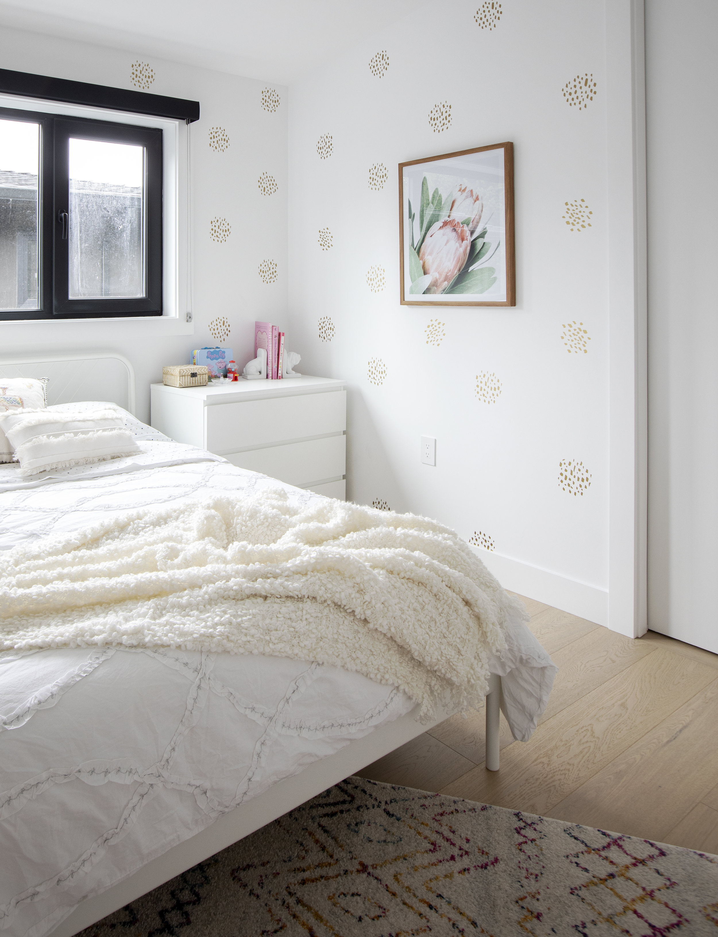 An older child's bedroom in East 13th Street has a decorative wallpaper with clusters of little gold dots.