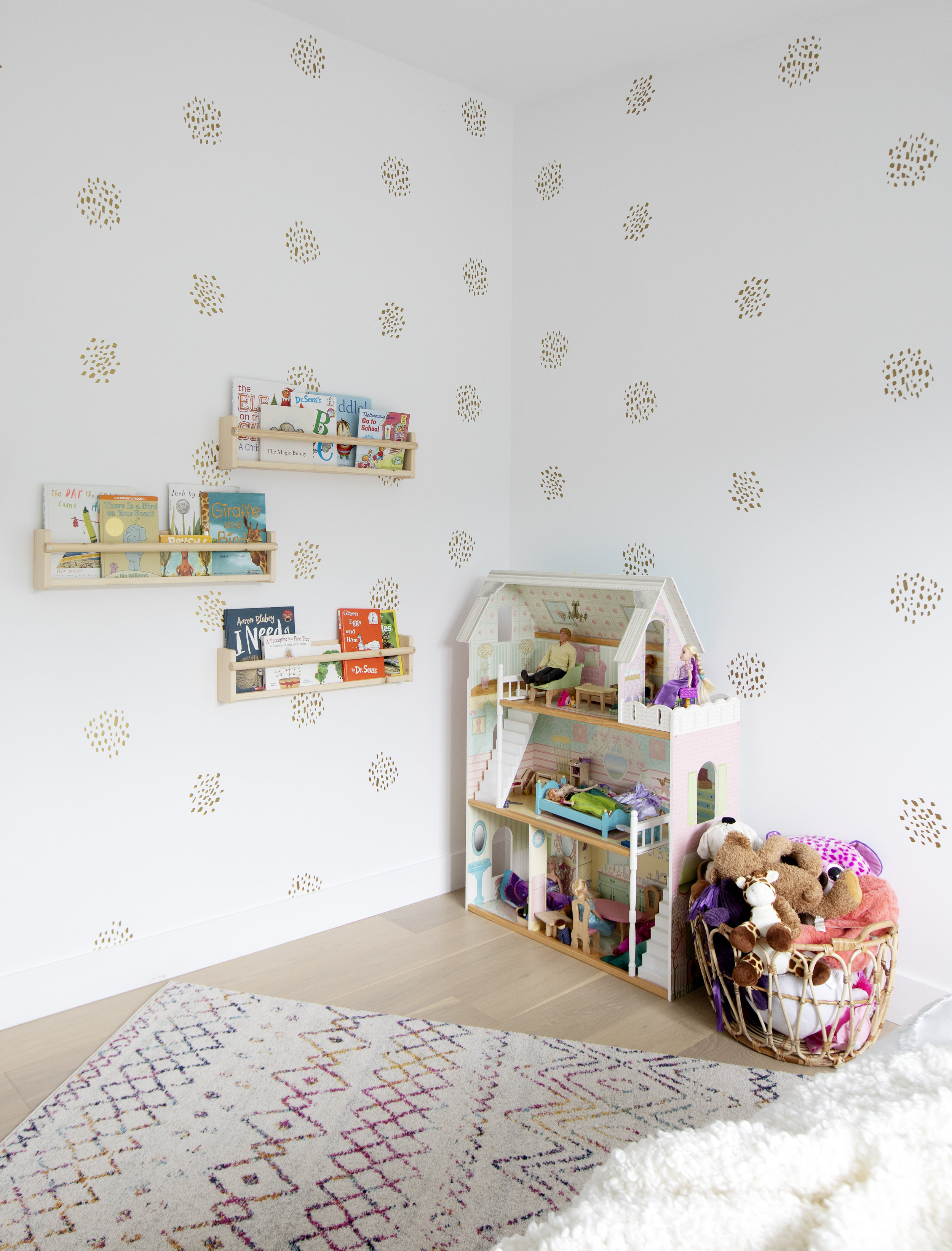 The corner of an older child's bedroom is home to a dollhouse and basket of stuffed animals as well as a custom book shelving affixed to the wall.