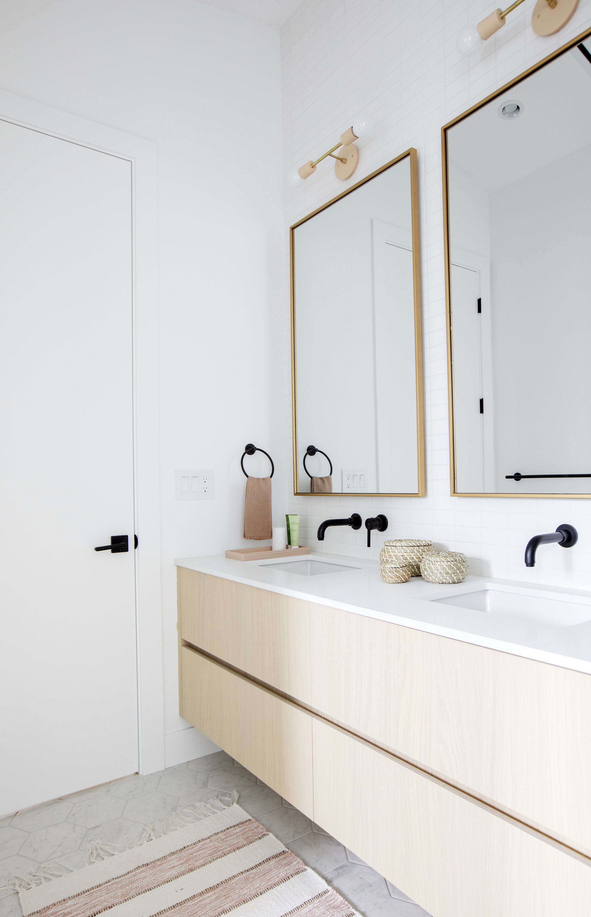 A bathroom in East 13th street, complete with double sinks and large rectangular mirrors.