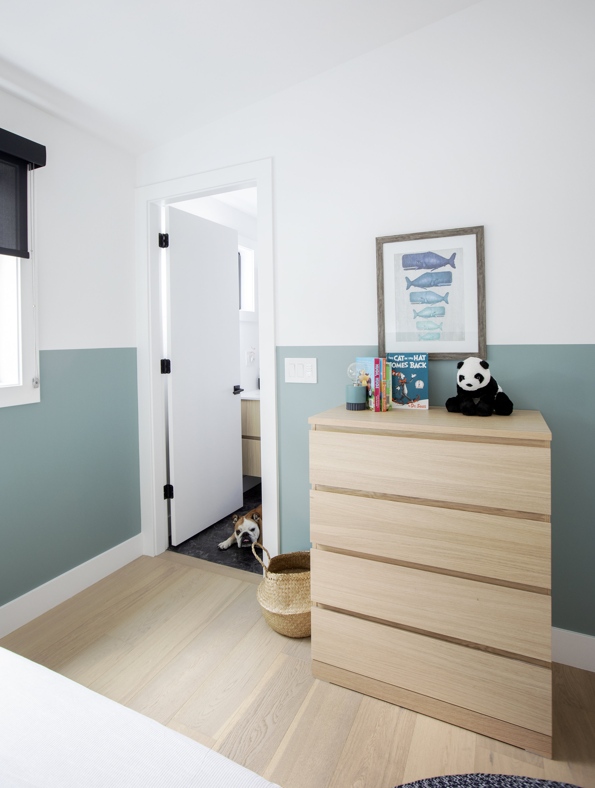 Opposite the twin bed in the third child's bedroom is a large light wood dresser drawer, sitting next to the bathroom, where a bulldog, who is a good boy, rests on the dark tile.