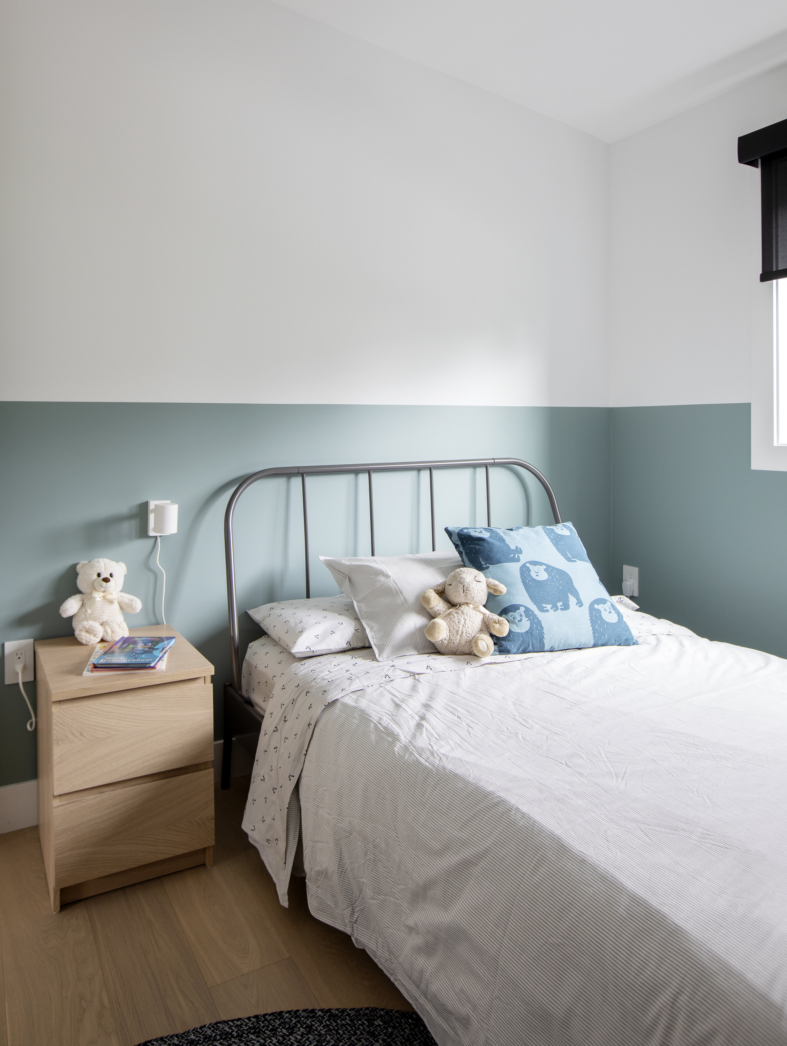 A third child's bedroom in East 13th street has walls where the top is painted white and bottom in blue. A steel twin bed sits in the corner.