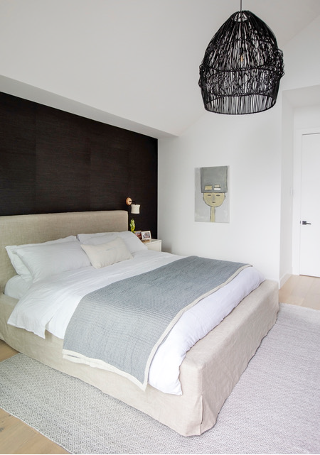 A Queen size bed with fabric headboard sits in front of an dark accent wall, with a black wicker light fixture hanging above.