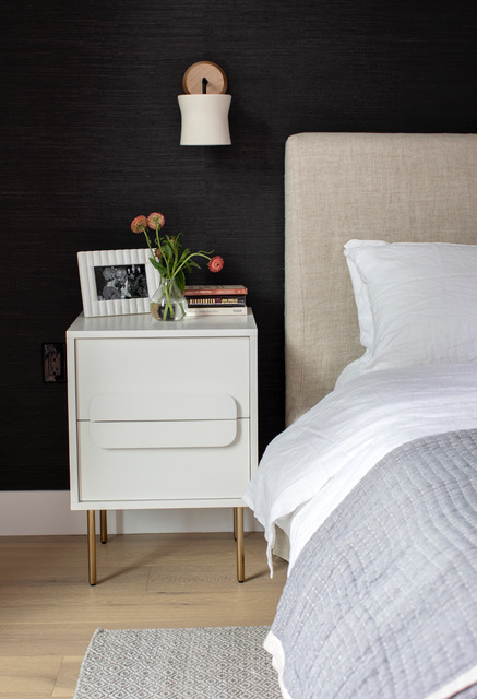 The master bedroom at East 13th Street has a side table with brass legs next to a bed with a fabric headboard.
