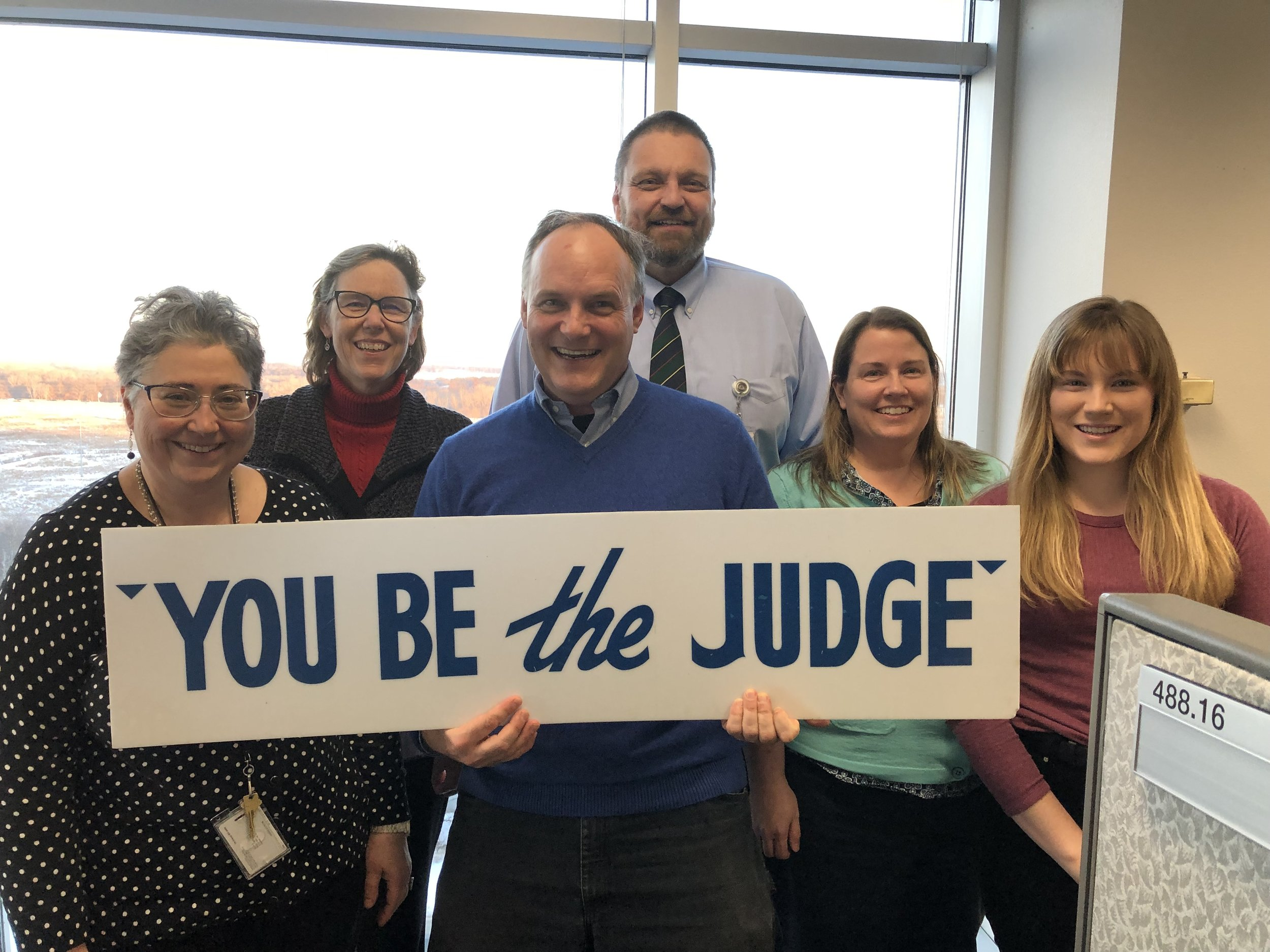 """Wisconsin Department of Agriculture, Trade & Consumer Protection - Thanks to Legal Counsel Cheryl Daniels, State Bar leader and former League of Women Voters President and ALJ, for the gift of the """"You Be the Judge"""" sign. Pictured with Cheryl & Paul are friends & former DATCP colleagues: Atty Liz Kennebeck, Atty Paul LaZotte, Atty Sheri Walz, and Public Records Specialist Bridget Frick."""