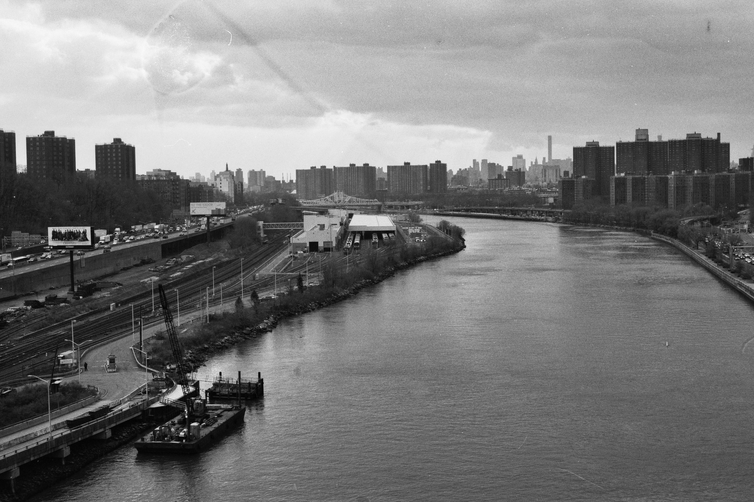 Looking south towards Uptown and Midtown from the High Bridge over the Harlem River with Highbridge, Bronx to the left of the frame and Washington Heights, Manhattan to the right.  Details :    film, 35mm Ilford Delta 400. Pentax K1000. Fletcher Berryman, 2018.
