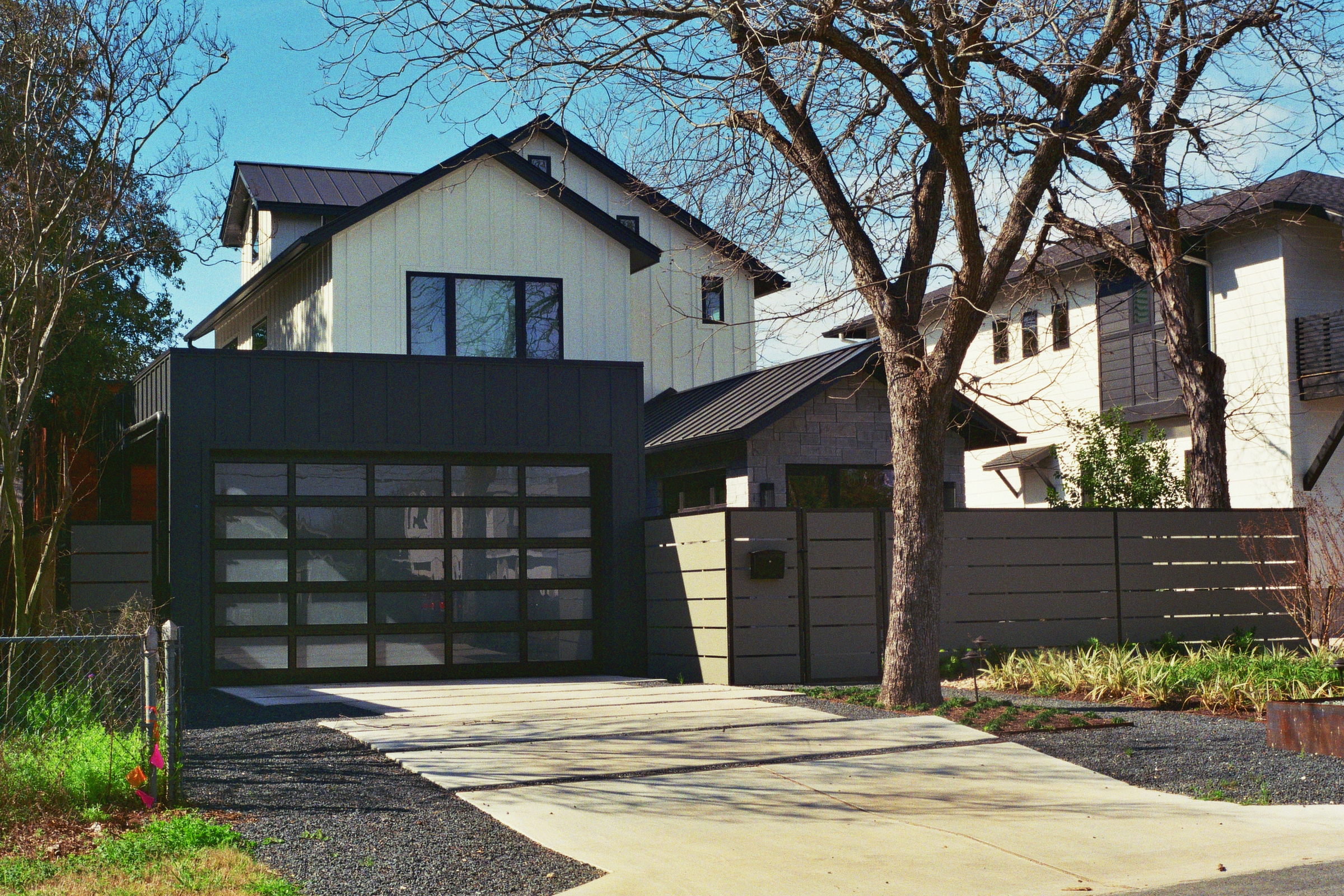 Modern homes stand beside older abodes in a hodgepodge typical of a gentrifying community.  Austin, TX  Kodak Ultra Max 400. Pentax K1000. Fletcher Berryman 2019.