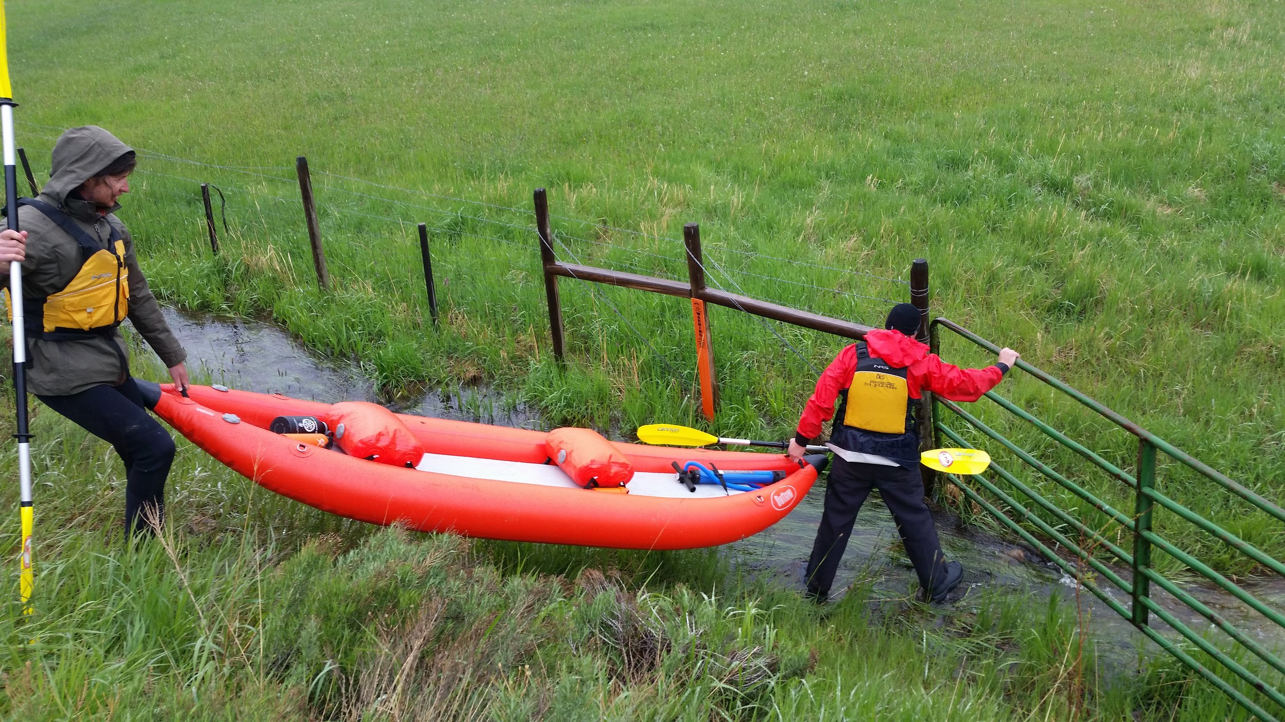 Lincoln and John load an inflatable kayak over a barbed-wire fence, shortly before loading into the Little Snake River in southern Wyoming. [Photo: Damien Willis]