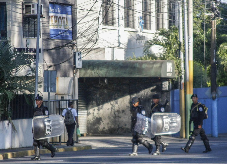 Riot police walk in front of the 100% Noticias cable and internet news station in Managua on December 22, 2018, a day after the station was raided and closed by the Nicaraguan police. Two journalists were arrested during the raid.  [Photo: AFP/Maynor Valenzuela]