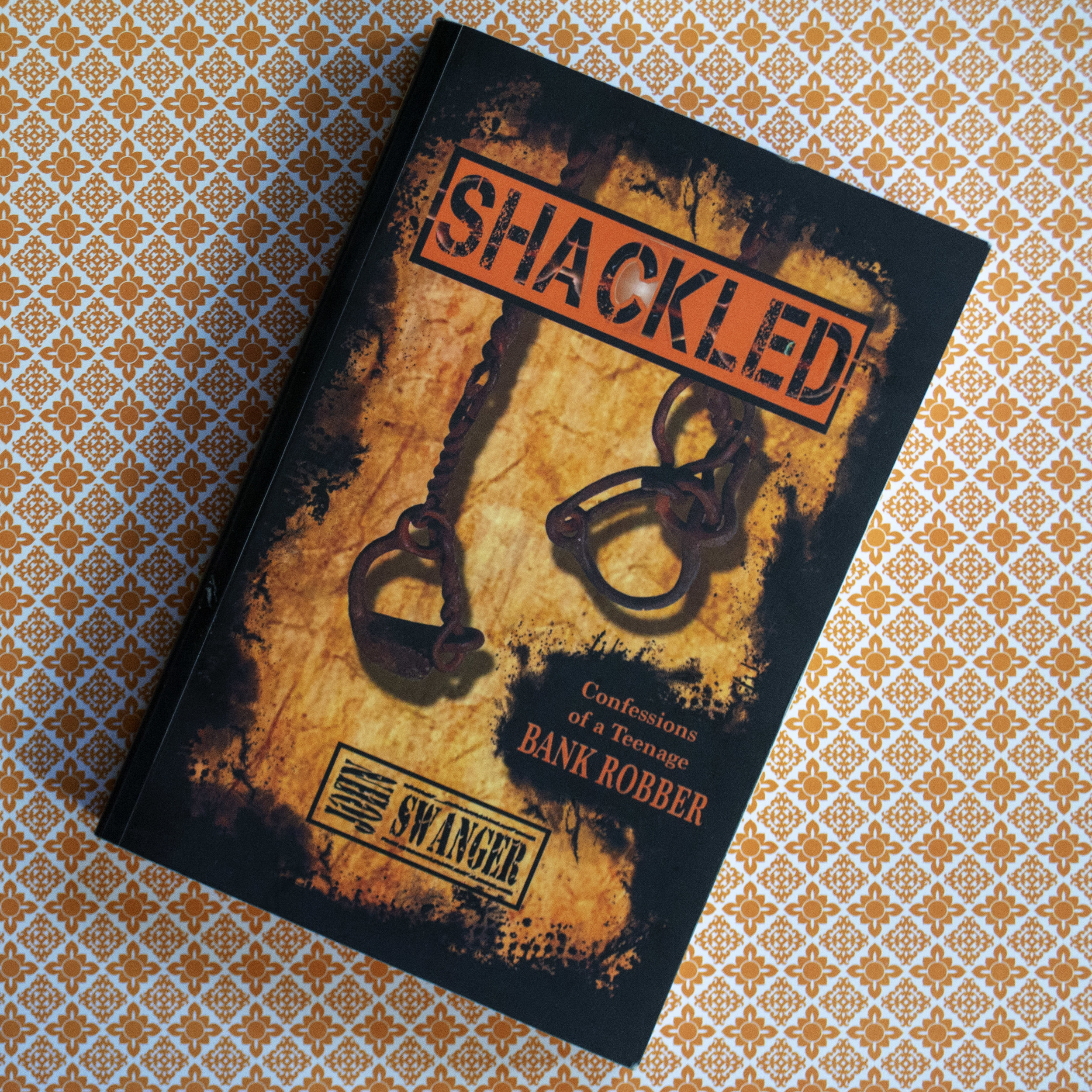 Shackled: Confessions of a Teenage Bank Robber - John Swanger - As a child, poverty and desperation sent John Swanger to live in orphanages and with countless relatives. When he was with his mother, they were constantly on the run, hiding from ex-husbands and irate landlords. At barely sixteen, John was kicked out of his shattered family by stepfather number three, onto the street where survival meant hustling pool and selling drugs. Bad choices bring consequences and by the age of 18, it was time to pay up.John Swanger tells the riveting story of his years as a teenage boy, eager for the loving father he never had. When he finally finds him, however, the older man turns out to be a bank robber, so John becomes one too. A gripping and dramatic tale of the life of teenage bank robber … and how God miraculously saved him.Also check out John's sequel, also produced by Inspira, Unshackled: A Story of Redemption.Learn more on John's website: www.johnswanger.org