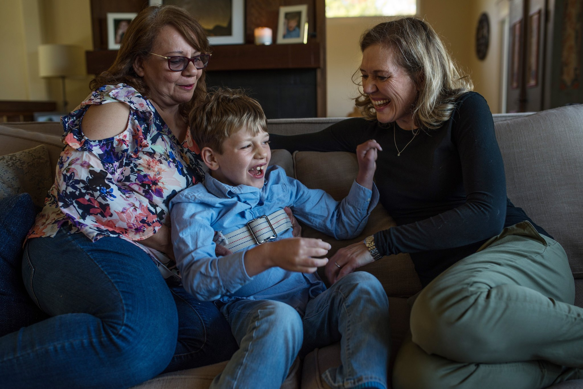 From left: Margarita Sanchez, Ben's nanny, Ben and Catherine at home. Ben wears a strap to prevent him from falling when he has his seizures. September Dawn Bottoms for The New York Times