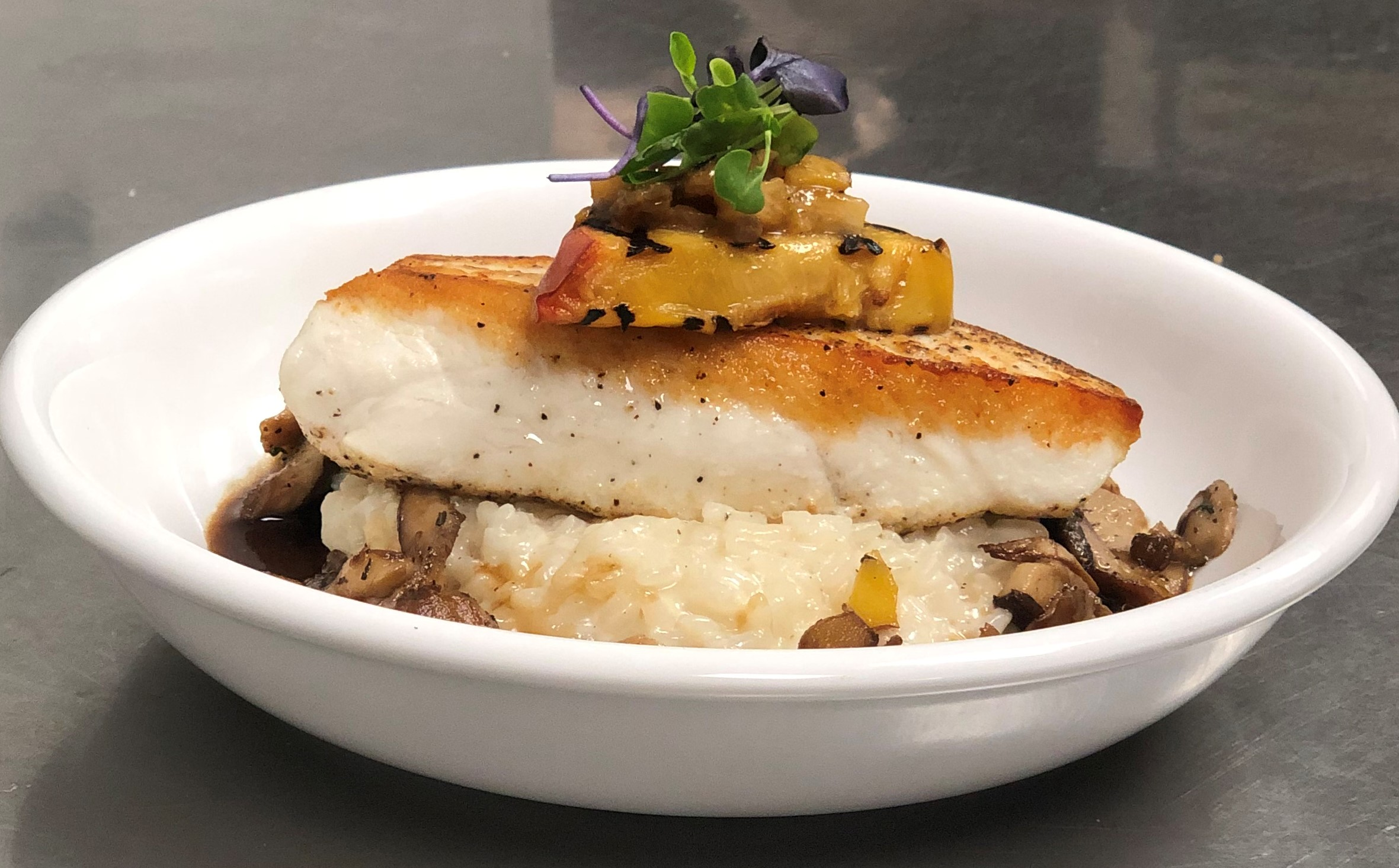 CAFÉ THYME |  Local CA halibut with porcini broth, peach chutney, grilled peach, risotto, and mixed micro greens.