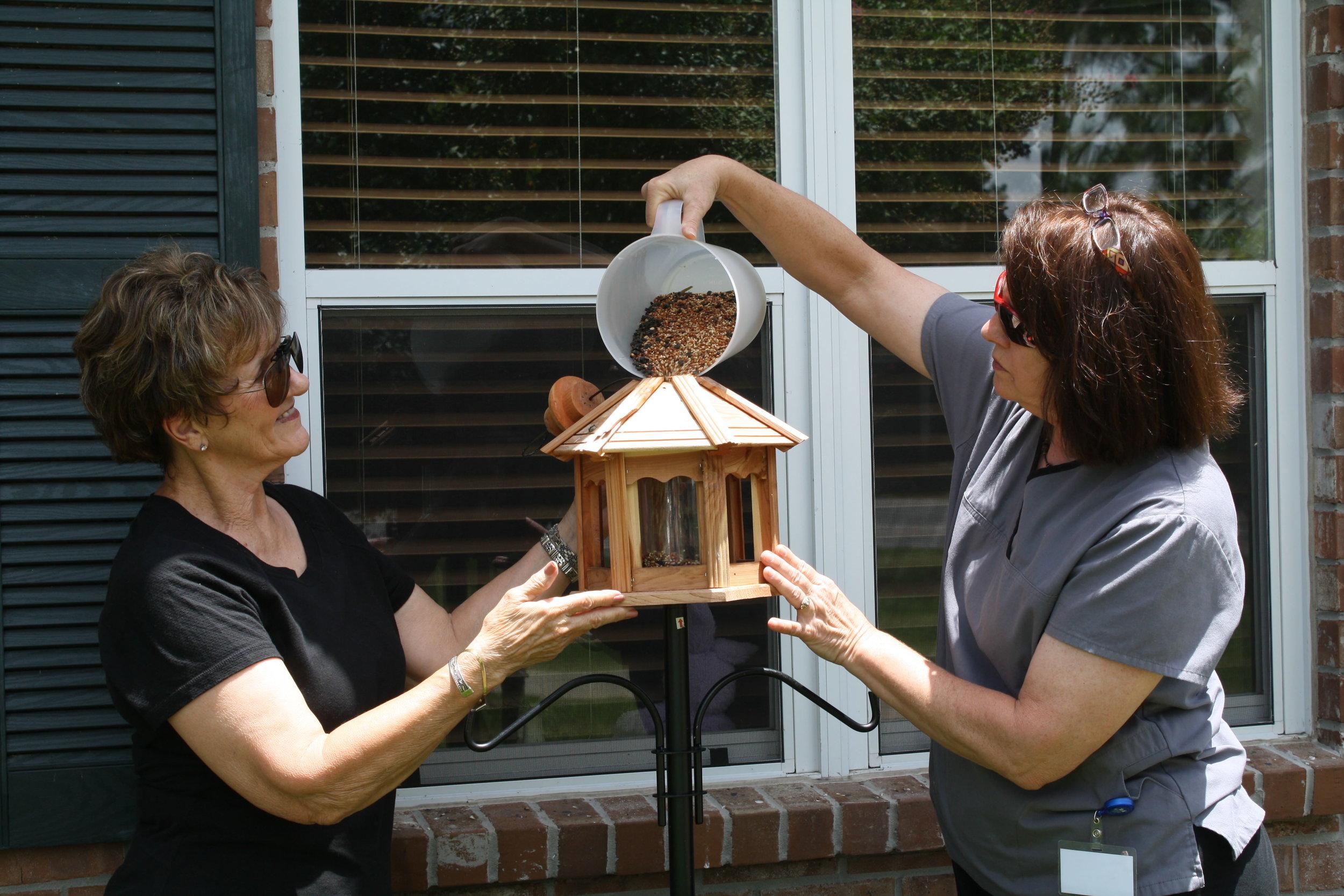 Jane Jarreau and Blanche Jewell refill bird feeder