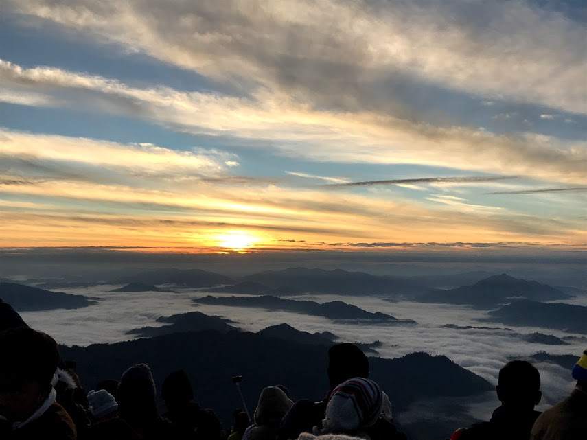 7:00 AM - The sun peaks over the horizon above a sea of fog and a crowded audience.
