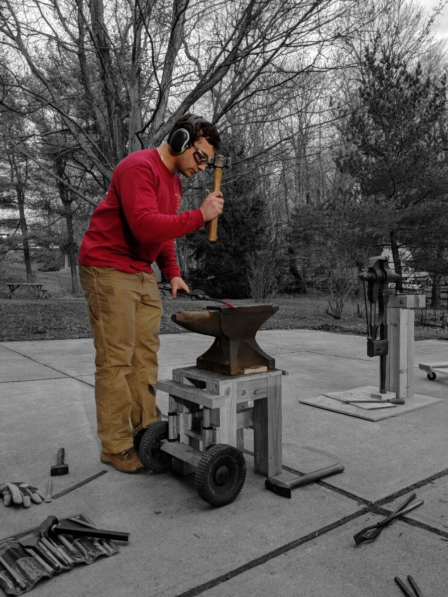 Me working at my first anvil I ever bought. The stand is less than ideal but it served me well for 2 years.