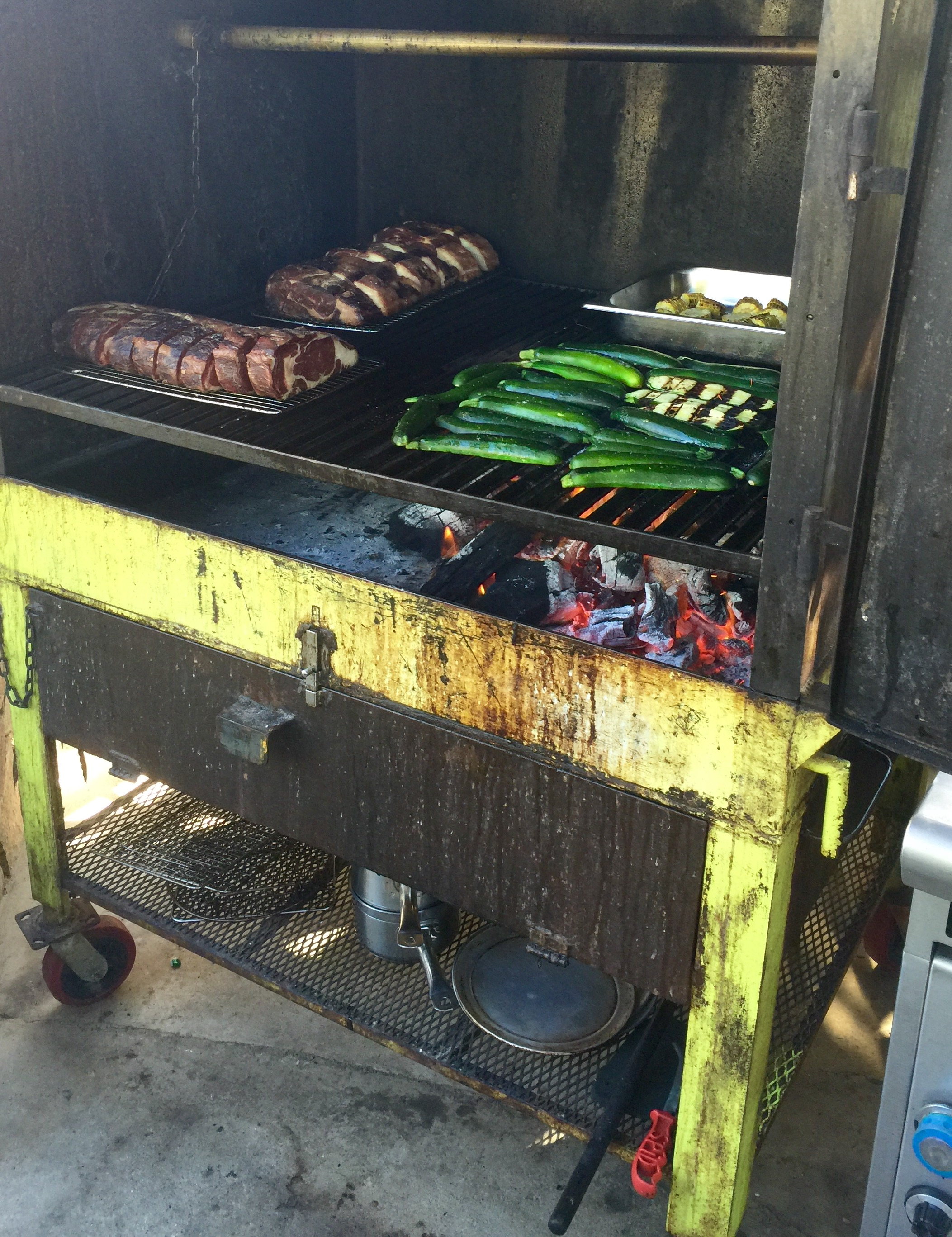 Ribeyes and zucchinis cooking on the custom smoker grill at Trans Lomita.