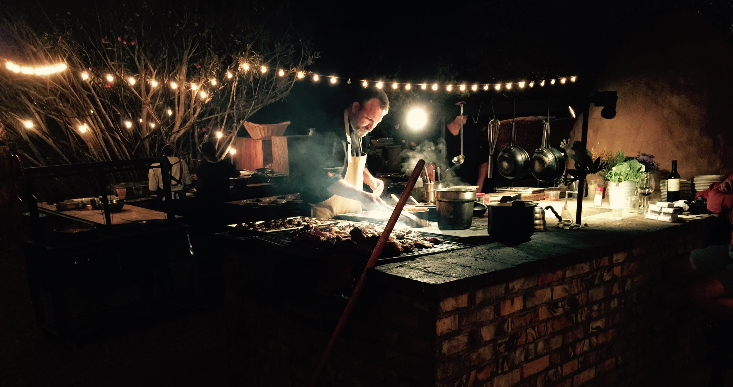 Drew cooking at night in his outdoor kitchen at Deckman's.