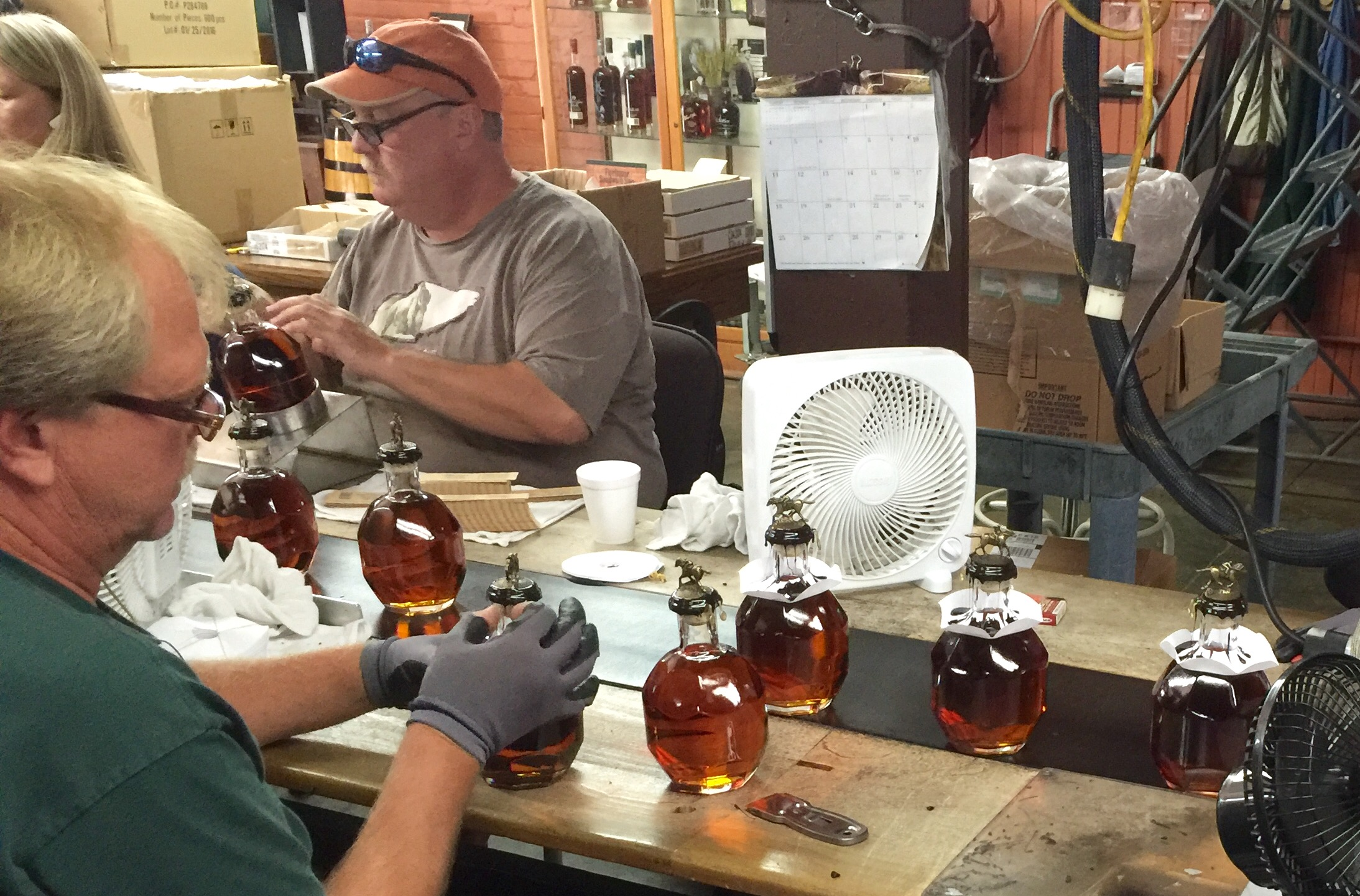 Blanton's hand bottling line at Buffalo Trace.  Those white paper collars are put on the bottles temporarily to catch any wax drips after the corks have been sealed with hot wax.