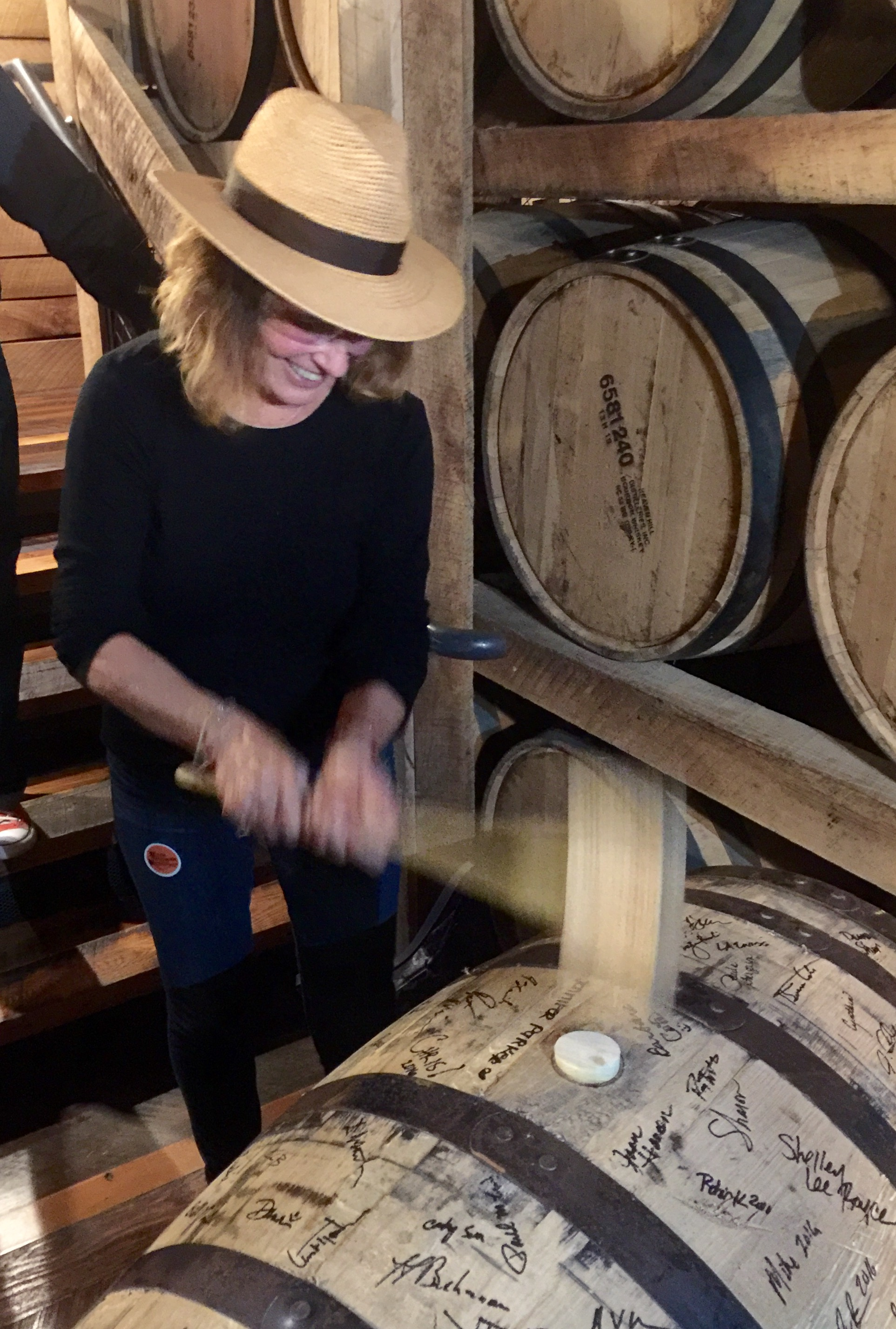 Bunging (hammering in the bung) barrel #667 at Evan Williams Bourbon Experience.
