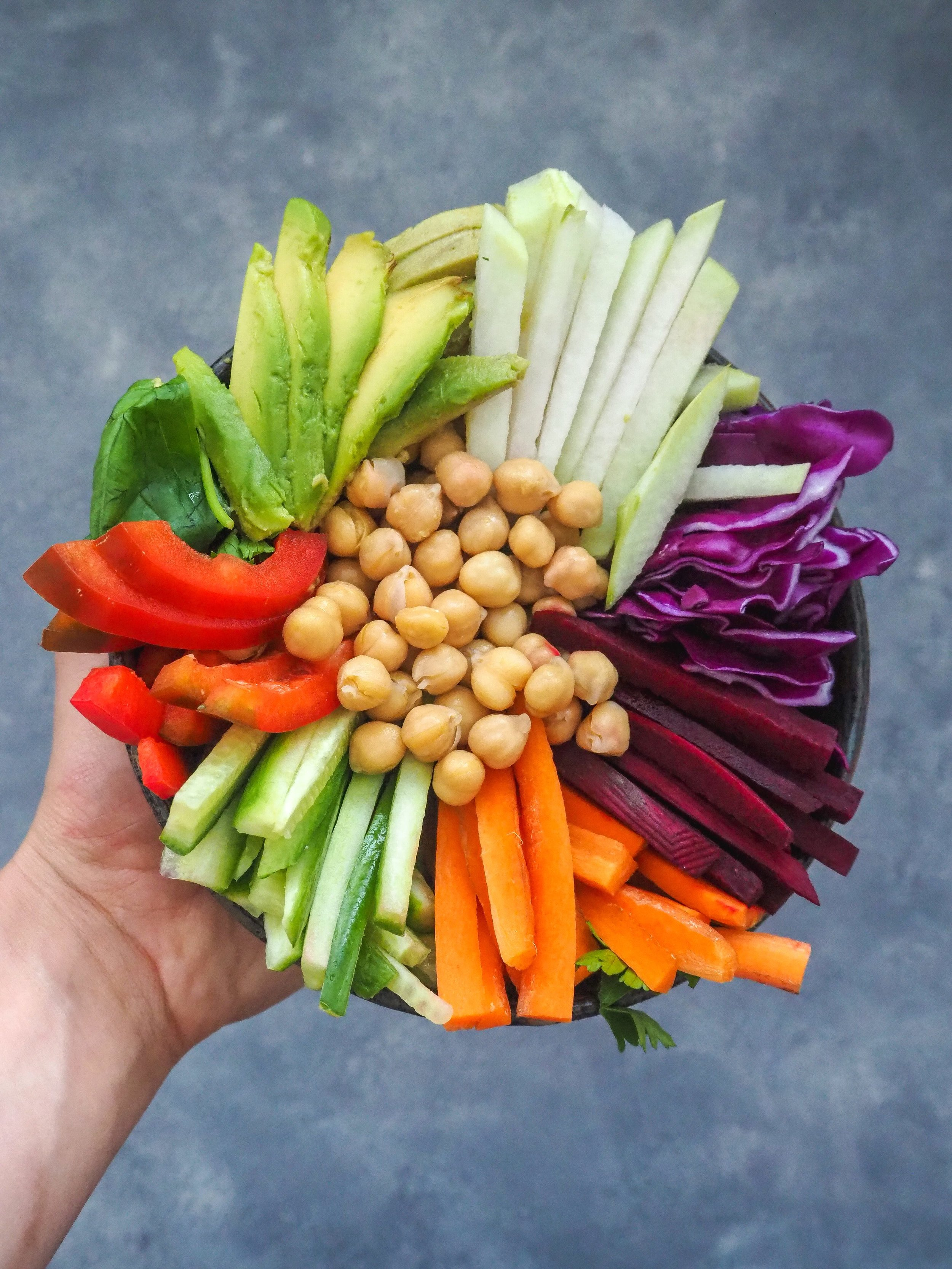 Carrots, cucumber, red pepper, raw beet, red cabbage, kohlrabi, avocado, lettuce, chickpeas, basil, and romaine lettuce in a bowl.