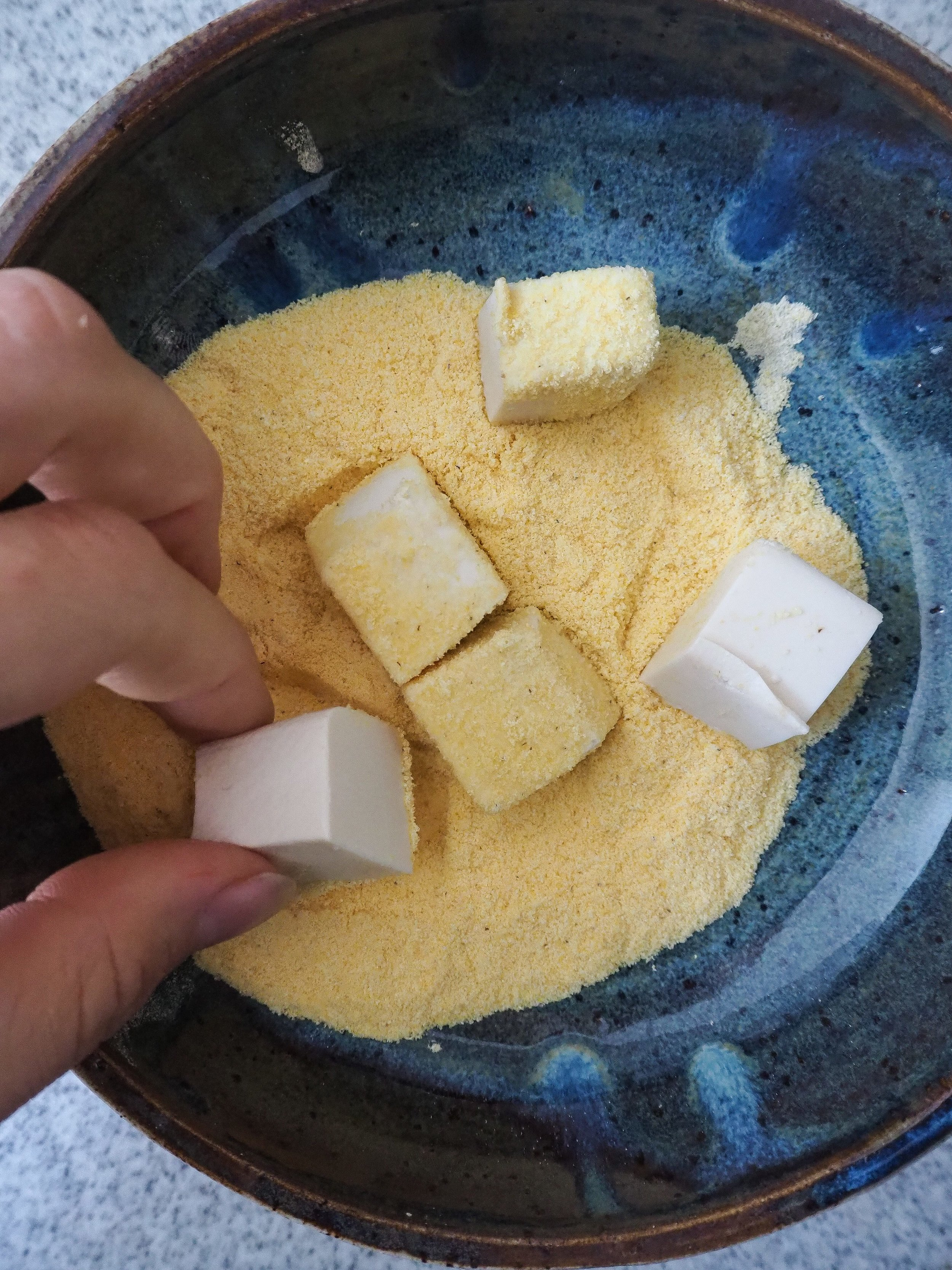 Coat the tofu in cornmeal.