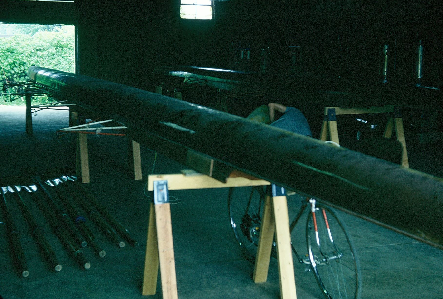 The club's first set of equipment on sawhorses in the warehouse — boats purchased from Windsor Boat Club, oars from Michigan State University. June 1976.