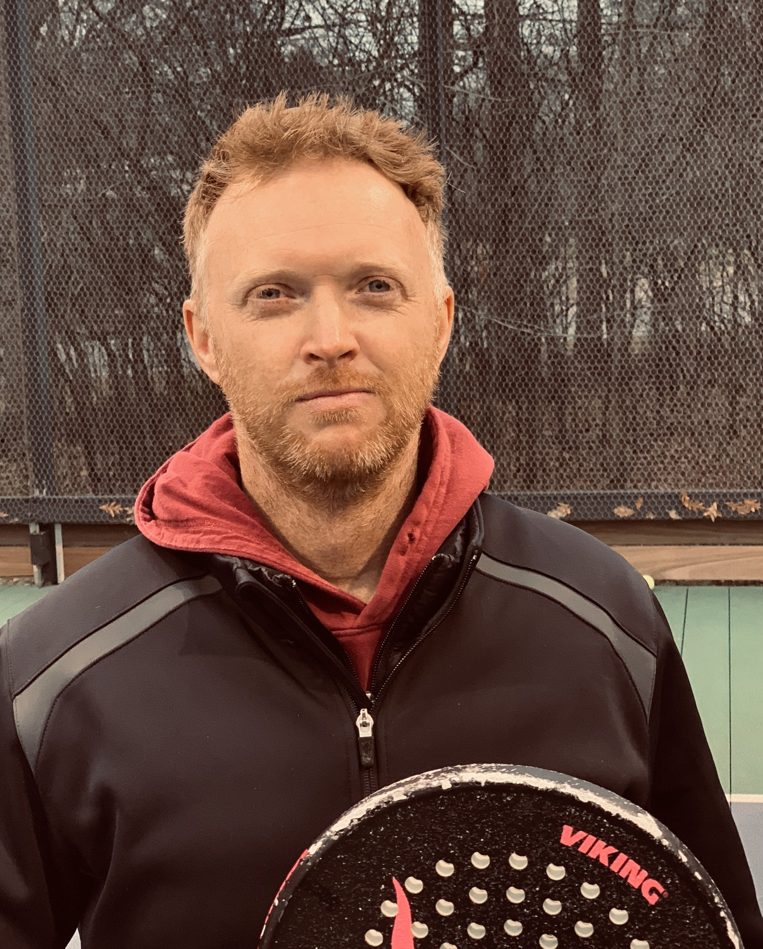 """Ben Ashford - is the Director of Racquet Sports at The Tennaqua Club in Deerfield, IL. Ben Ashford brings the accent to the Paddle Hacks """"Duo"""". His hobbies include petting his soccer ball and kicking his small dog around… wait, reverse it. Ashford brings the true talent to the team as he's the one with a real junior academy credentials and a short, yet mighty, pro-tennis career. Ben somehow manages to love and hate everyone at the same time. His English accent is """"rubbish"""" and his smooth, soft delivery will leave you wondering if his aggressive chains of expletives were even swear words at all. What a hack…Oh, how the mighty have fallen... into a pit… known as platform tennis."""