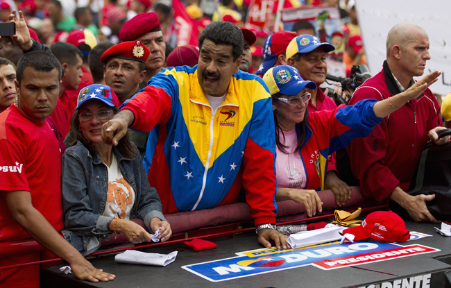 Venezuela's President Nicolas Maduro (C) greets supporters during a May Day rally in Caracas May 1, 2013. Opposition and government supporters flooded Venezuelan streets in rival May Day marches on Wednesday as a continuing dispute over the results of last month's presidential vote kept political tensions high in the OPEC nation. On Tuesday, opposition deputies were beaten in a fracas in Congress resulting from their refusal to recognize the presidency of Nicolas Maduro, who narrowly won the April 14 election triggered by the death of socialist leader Hugo Chavez. REUTERS/Carlos Garcia Rawlins (VENEZUELA - Tags: POLITICS) - RTXZ6SD