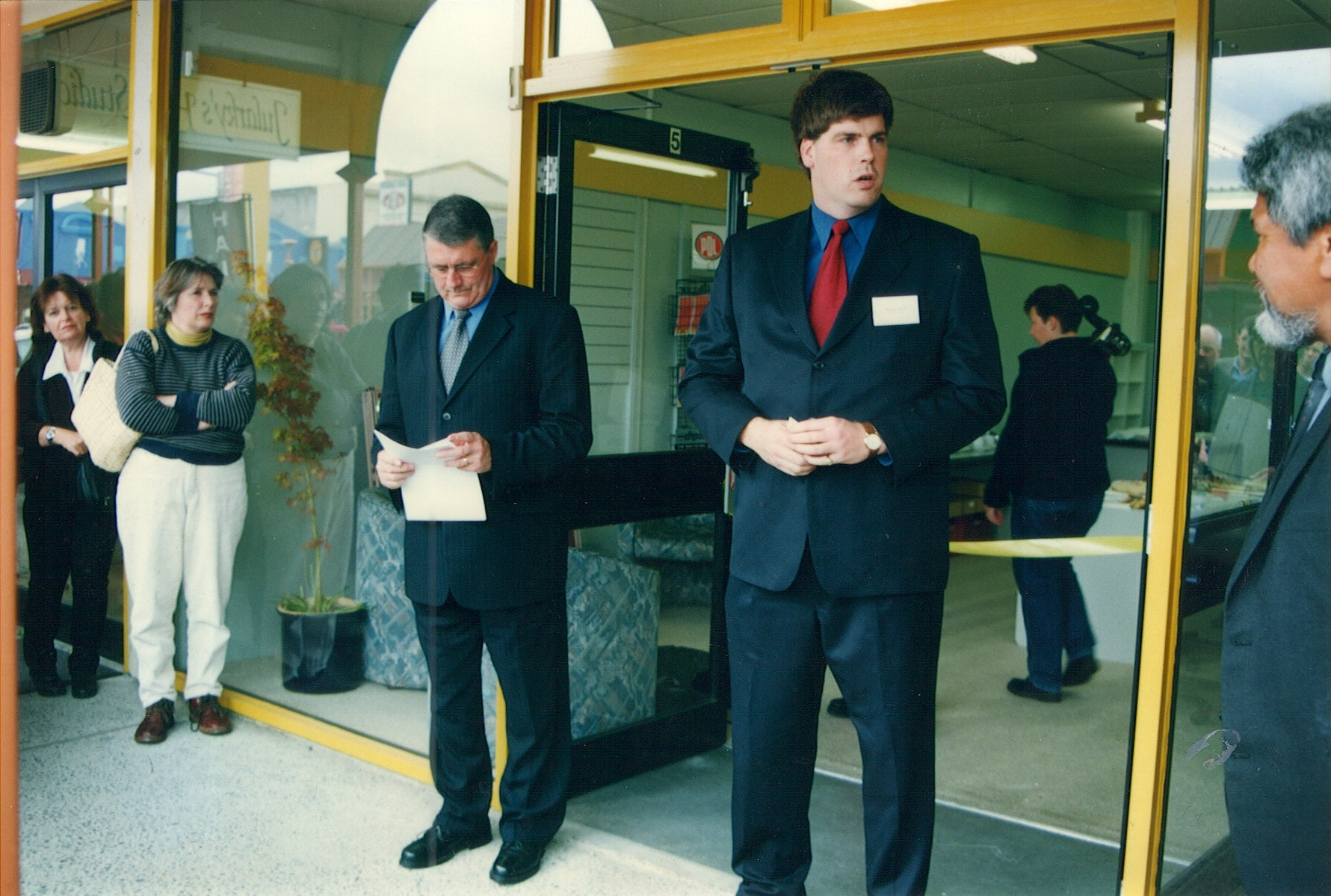 Deputy Prime Minister Jim Anderton (centre left) reviews his notes prior to delivering his speech officially opening Addington.net on 23 November 2001.