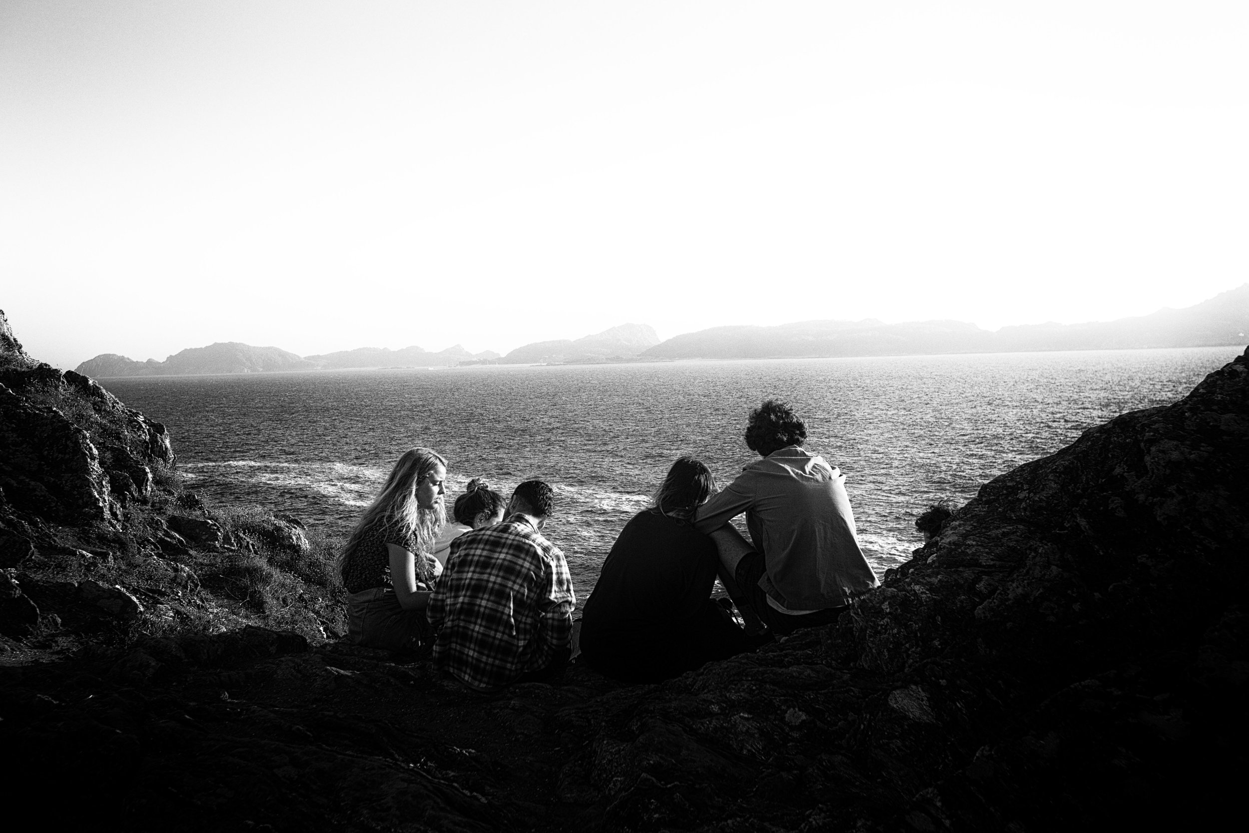 "A group of teenagers talk in front of the ocean, open sea, where the sun hides each afternoon. The image reminds me of my adolescence and the hormonal explosion that makes us dream and grow, unfortunately and unevenly in an unjust and aggressive world .  Somewhere near to the paradise. From ""Where Gods live"" photoessay. 2018"
