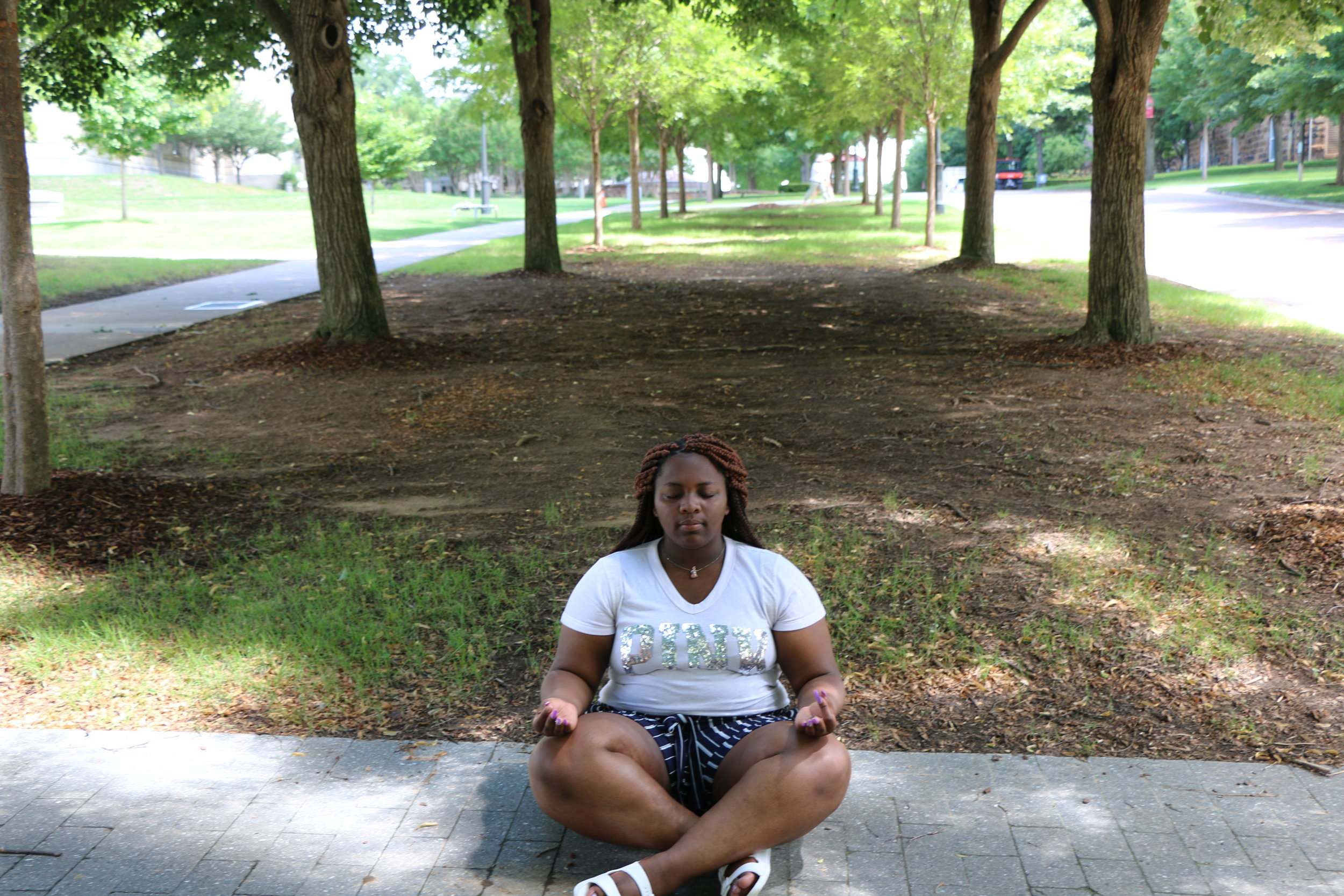 Aaliyah meditating in a Northwest Arkansas park.