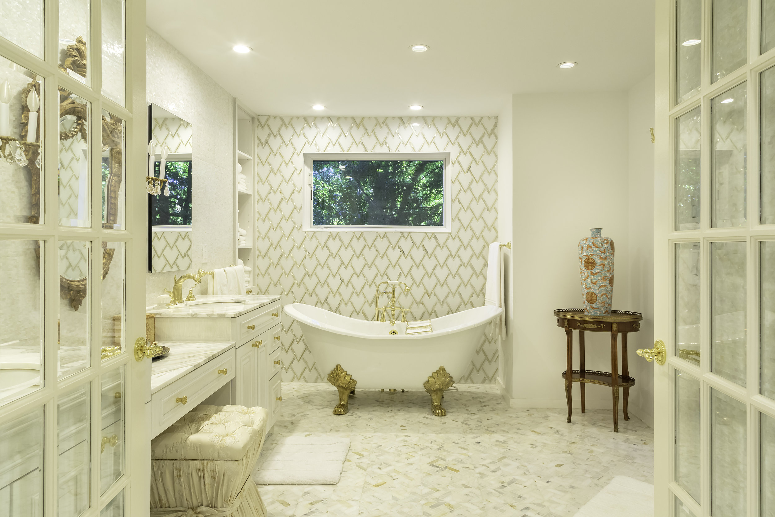 Large bathroom with golden hues and standalone plunge tub