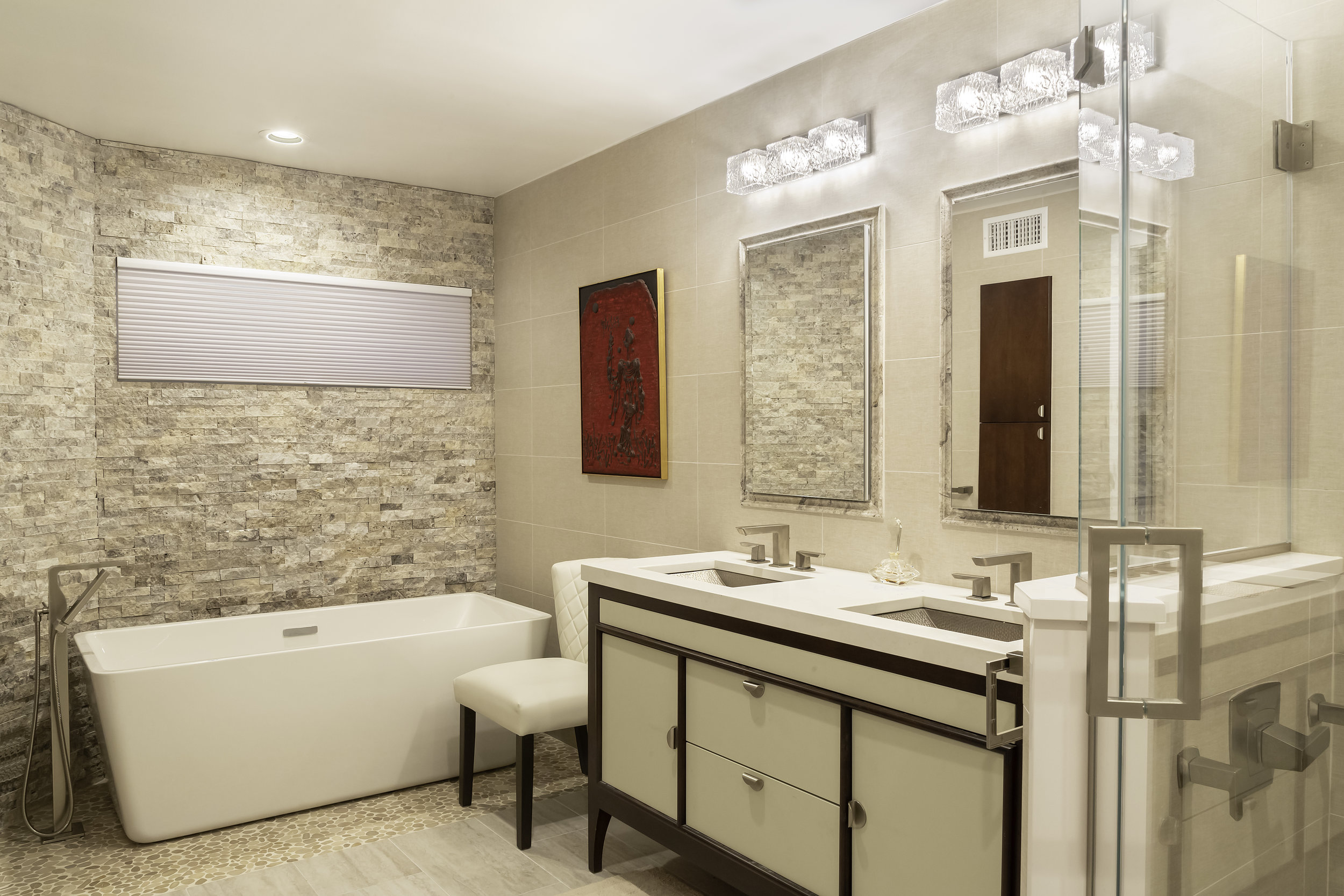 Cream colored bathroom with red painting hanging on wall
