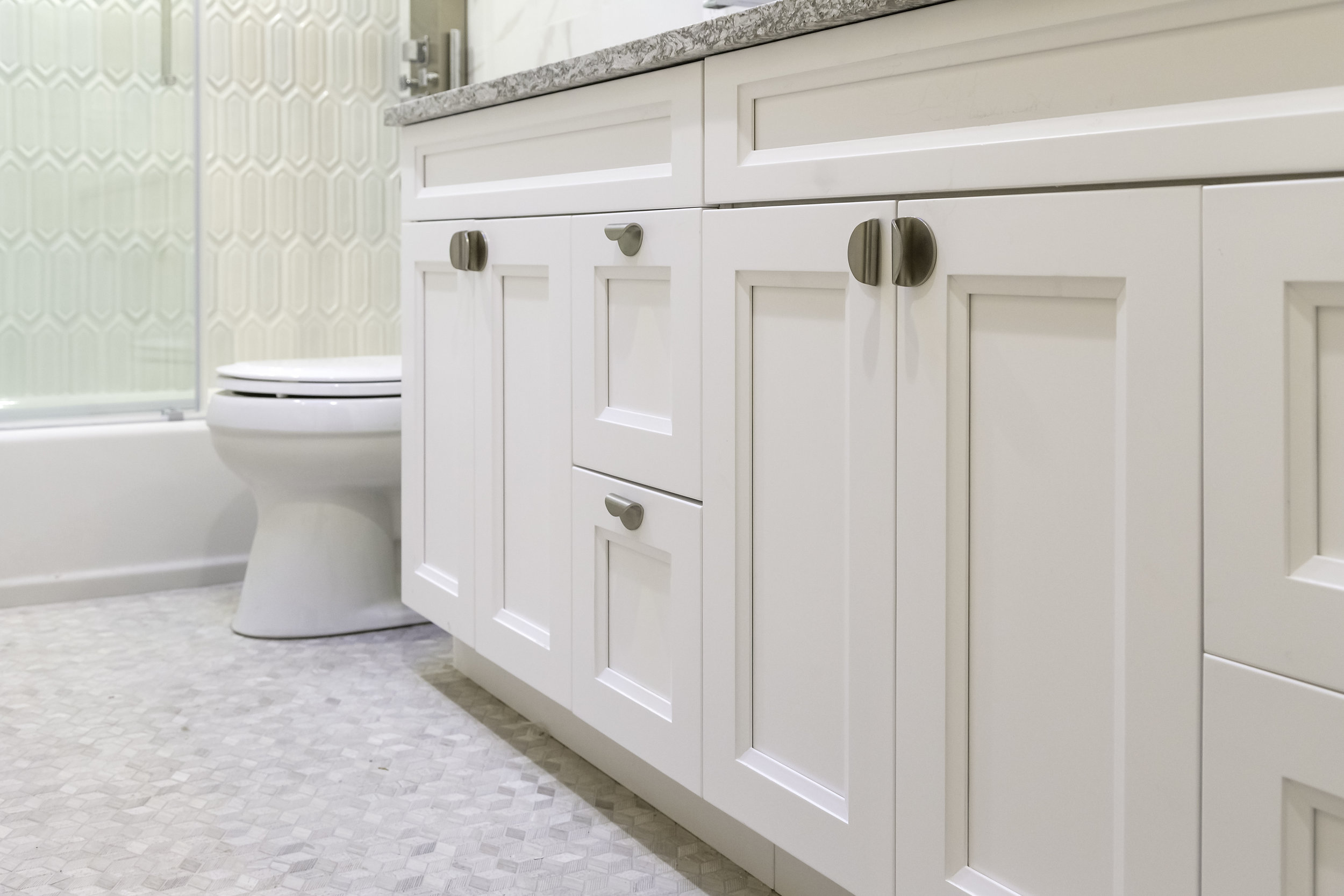 Bright bathroom with white cabinets and tiled floor