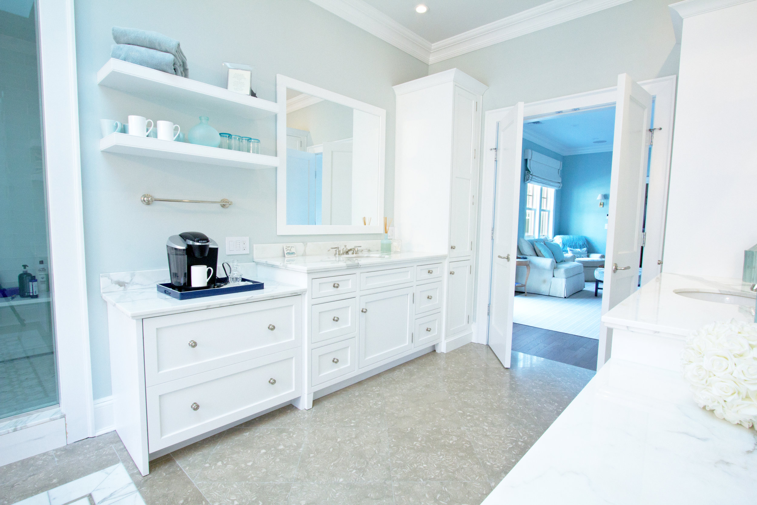Long bathroom with white cabinets and coffee station