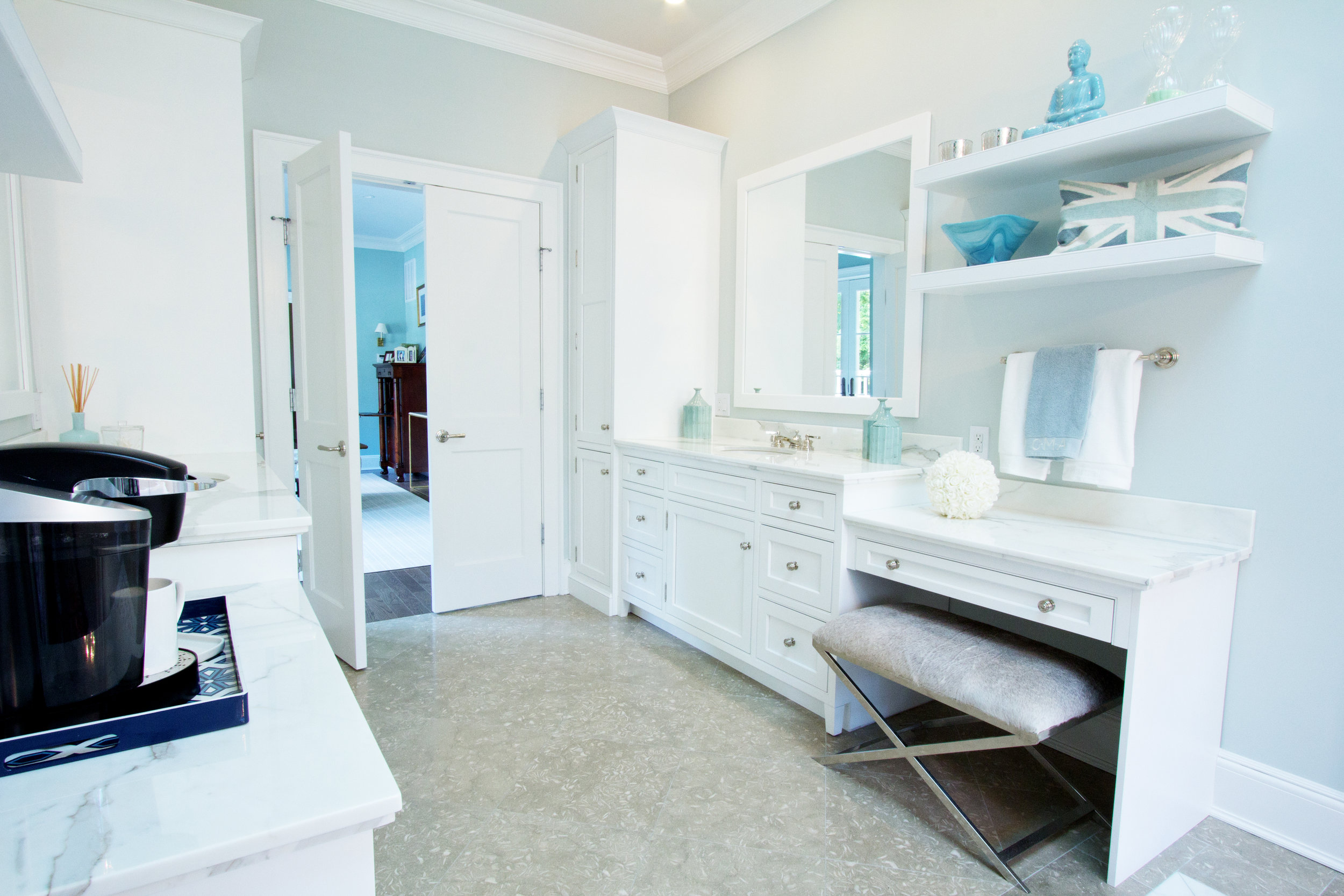 Long bathroom with white cabinets and seated vanity station