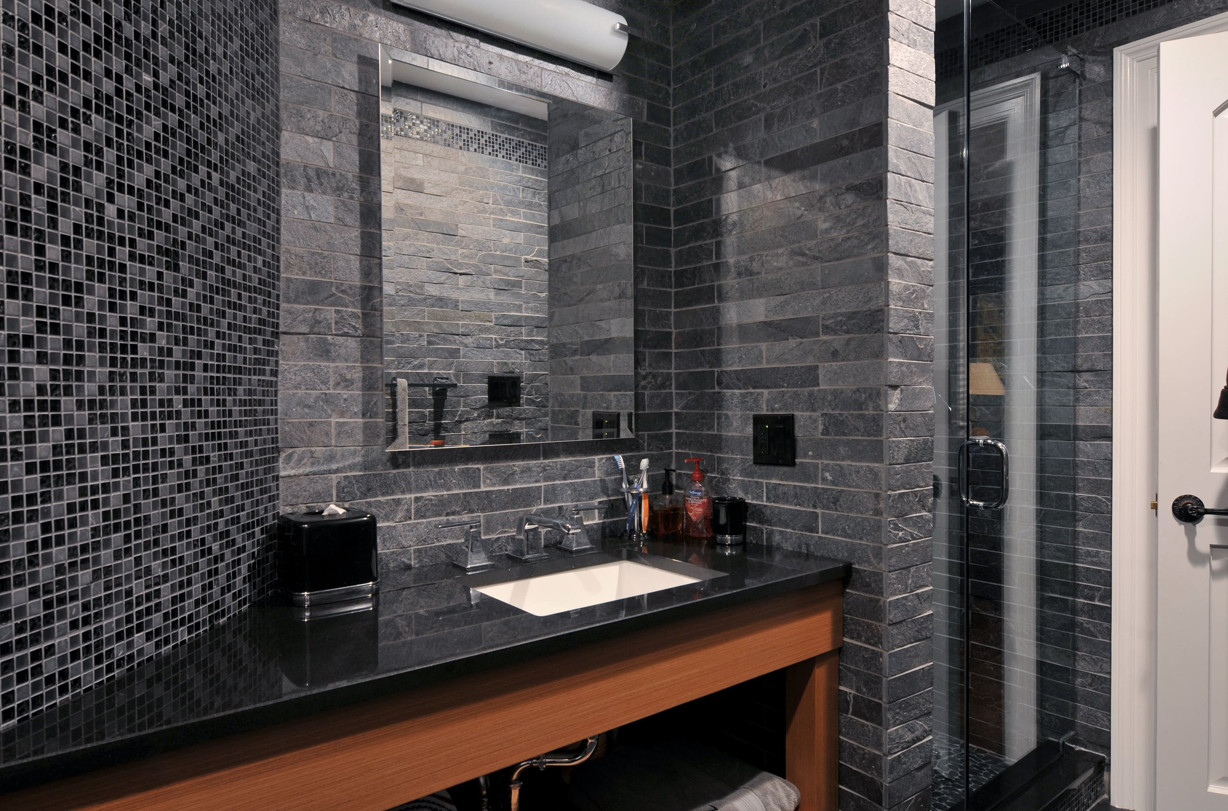 Bathroom with dark tile and black marble counter