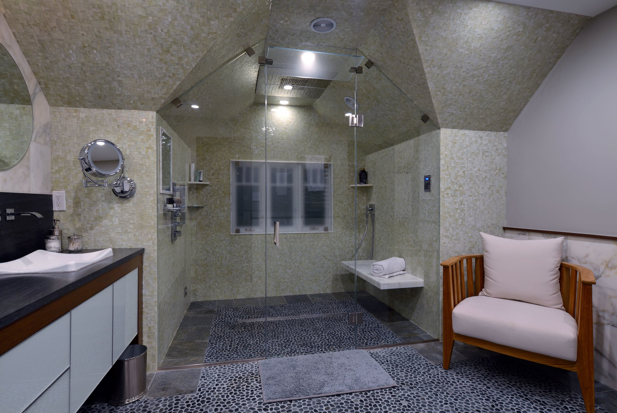 Large bathroom with peaked ceiling and glass walled shower with seat