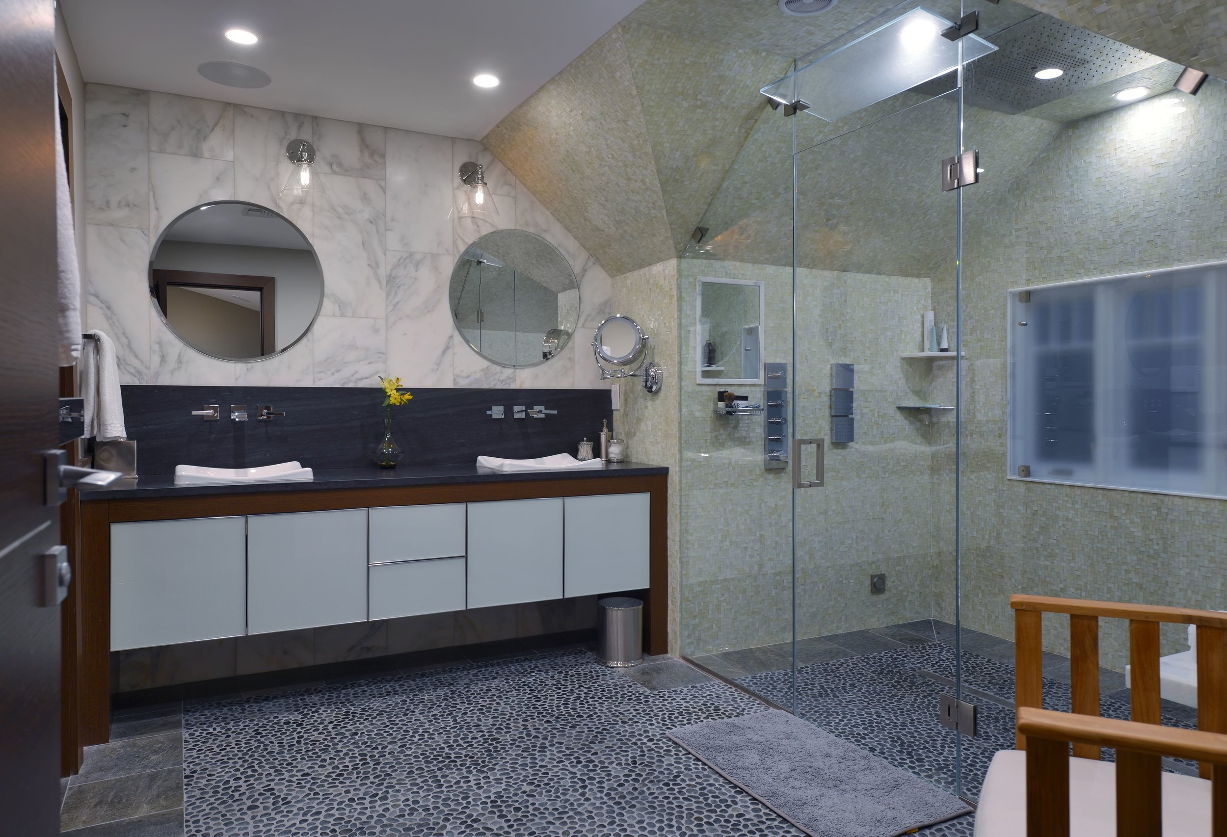 Large bathroom with double sinks and double circular mirrors hanging above