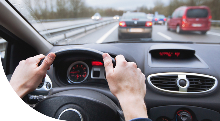 hands on steering wheel driving car on highway.jpg